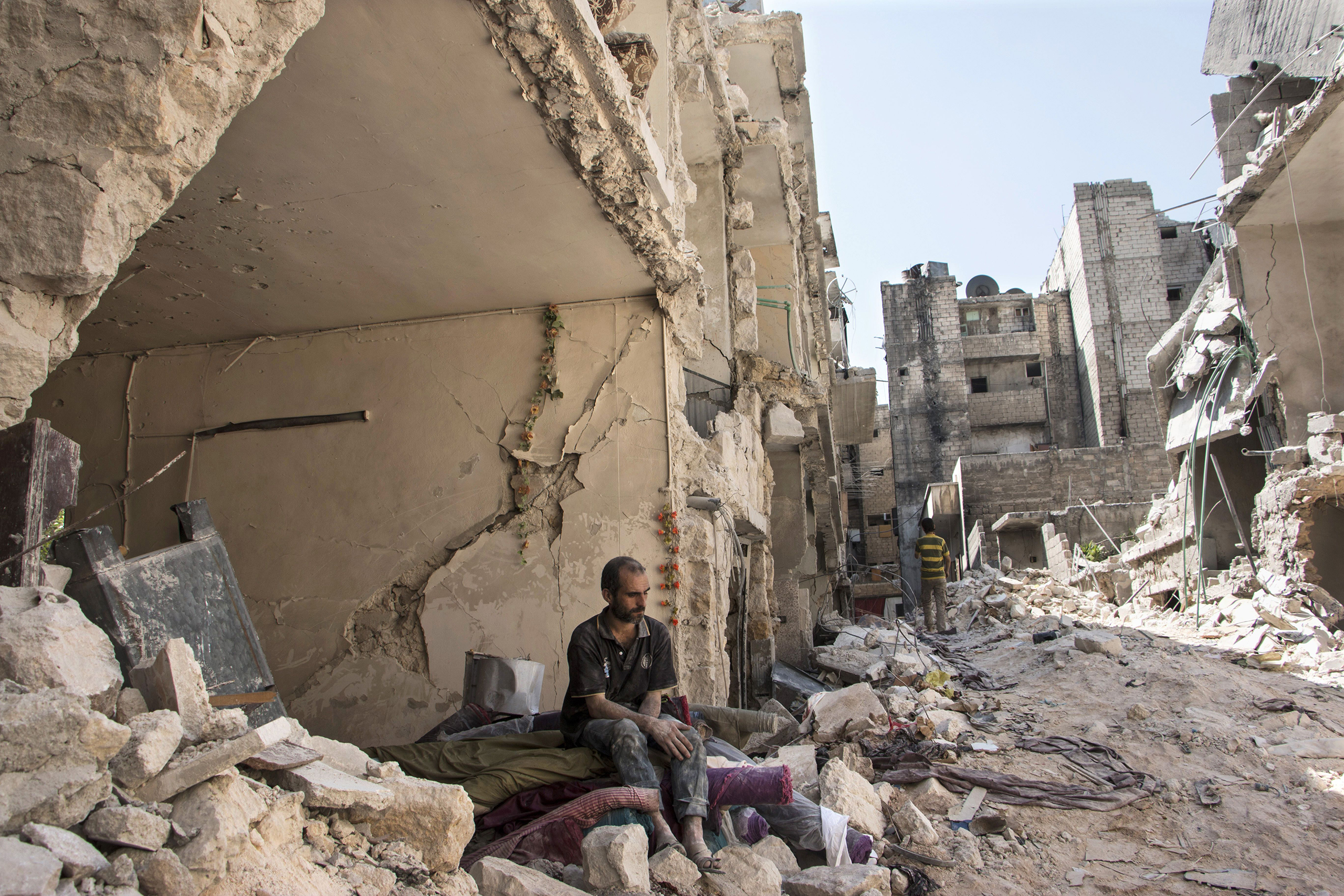 A Syrian man sits in the rubble following a barrel bomb attack the previous day on the rebel-held neighborhood of al-Mashad in Aleppo on Sept. 17, 2015.