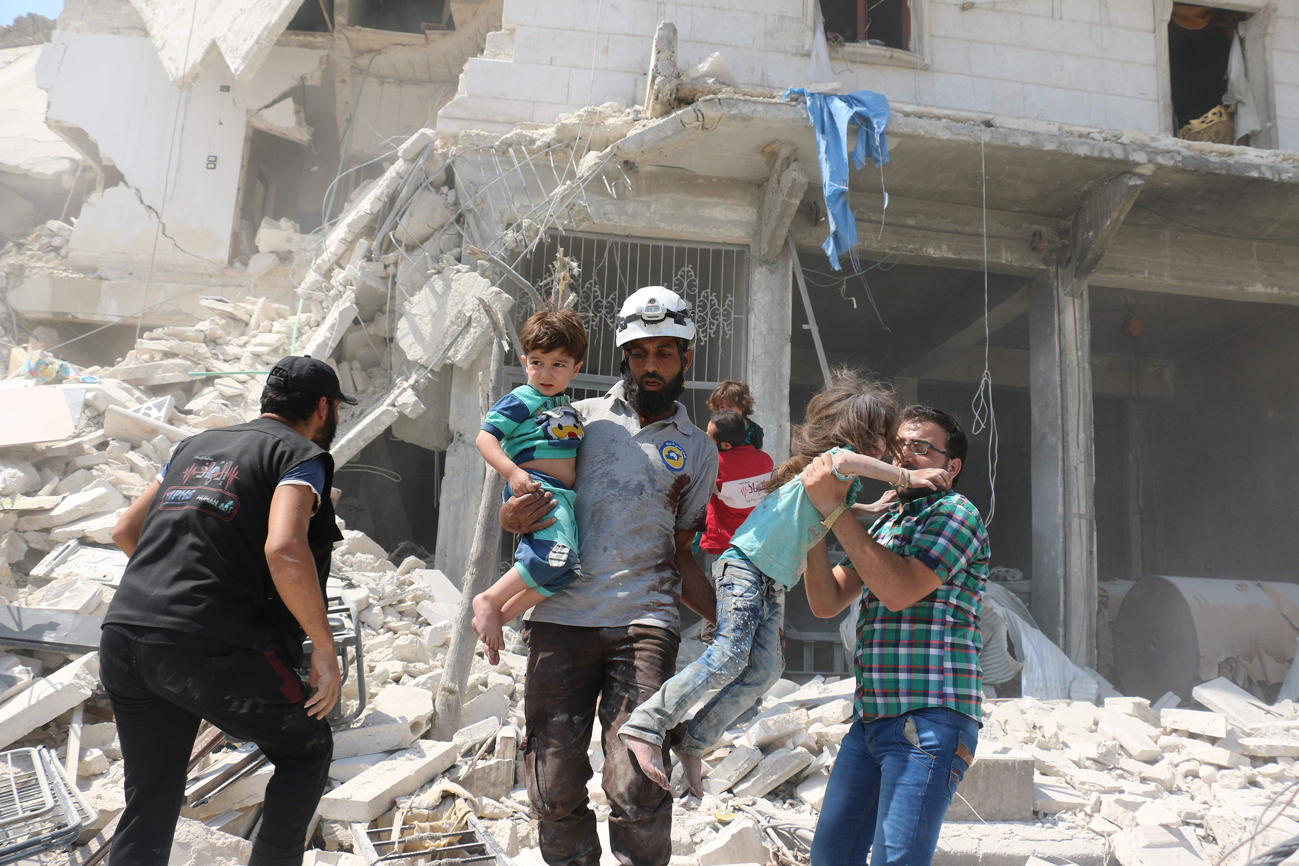 Syrian civilians and a rescue worker evacuate children in the Maadi district of eastern Aleppo after regime aircrafts reportedly dropped explosive-packed barrel bombs on Aug. 27, 2016.