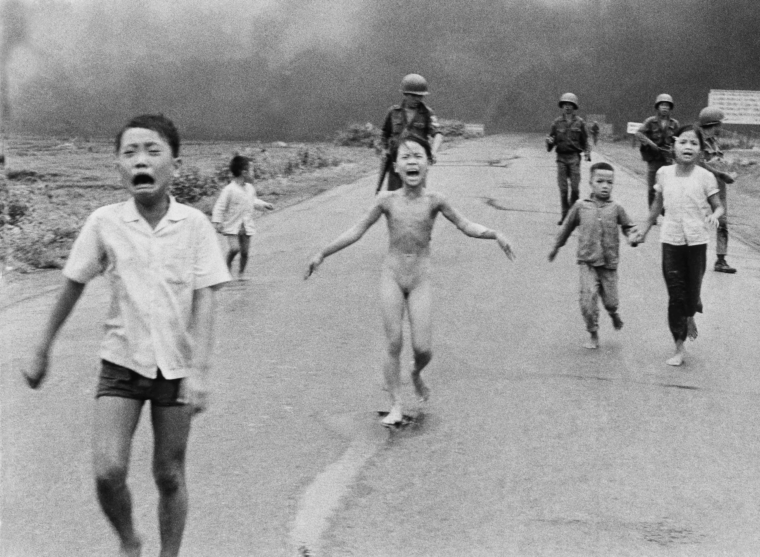 South Vietnamese forces follow after terrified children, including 9-year-old Kim Phuc, center, as they run down Route 1 near Trang Bang after an aerial napalm attack on suspected Vietcong hiding places on June 8, 1972.