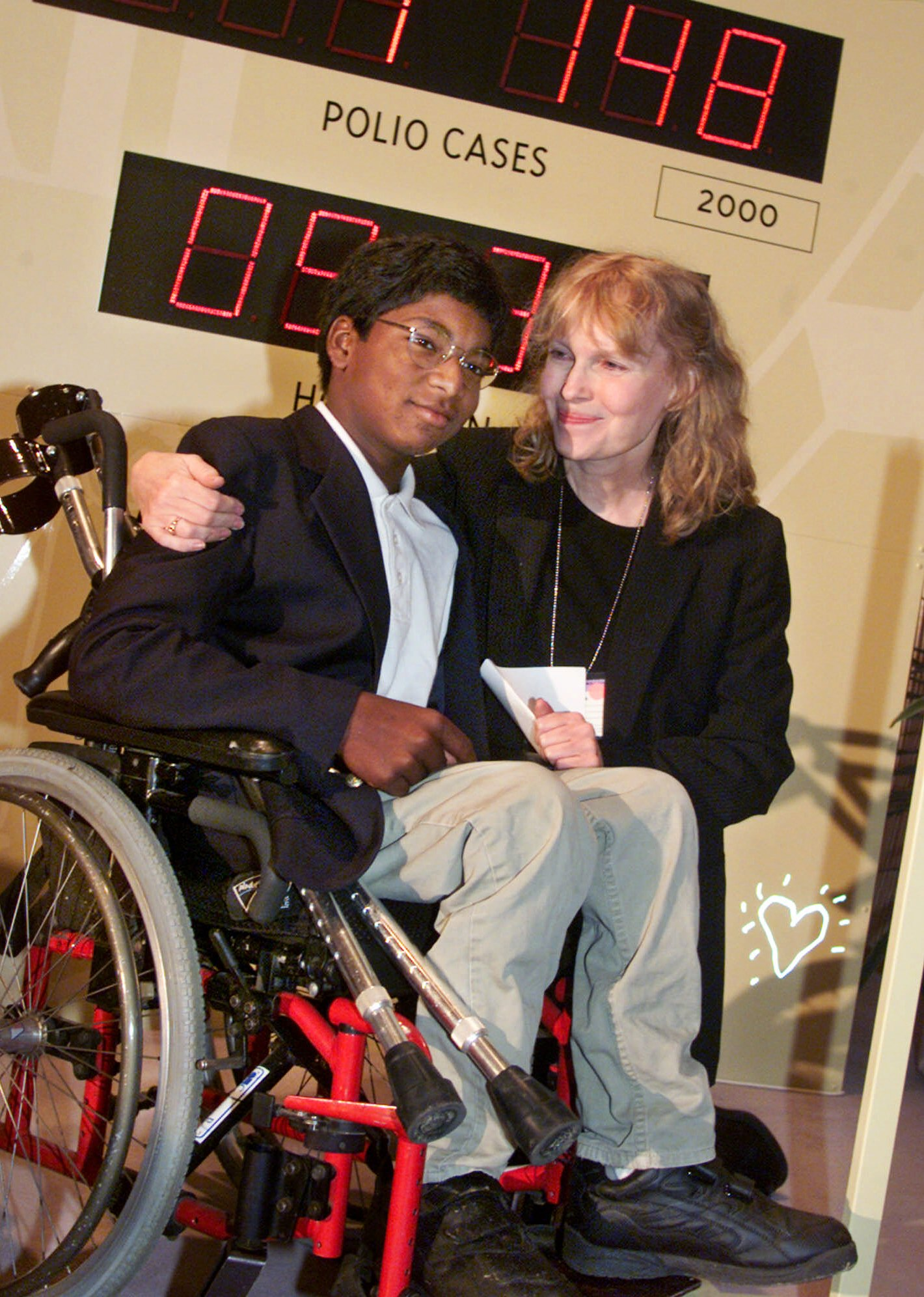 Actress Mia Farrow and her adopted son Thaddeus as they participate in the global summit on polio eradication, Sept. 27, 2000, at United Nations headquarters.
