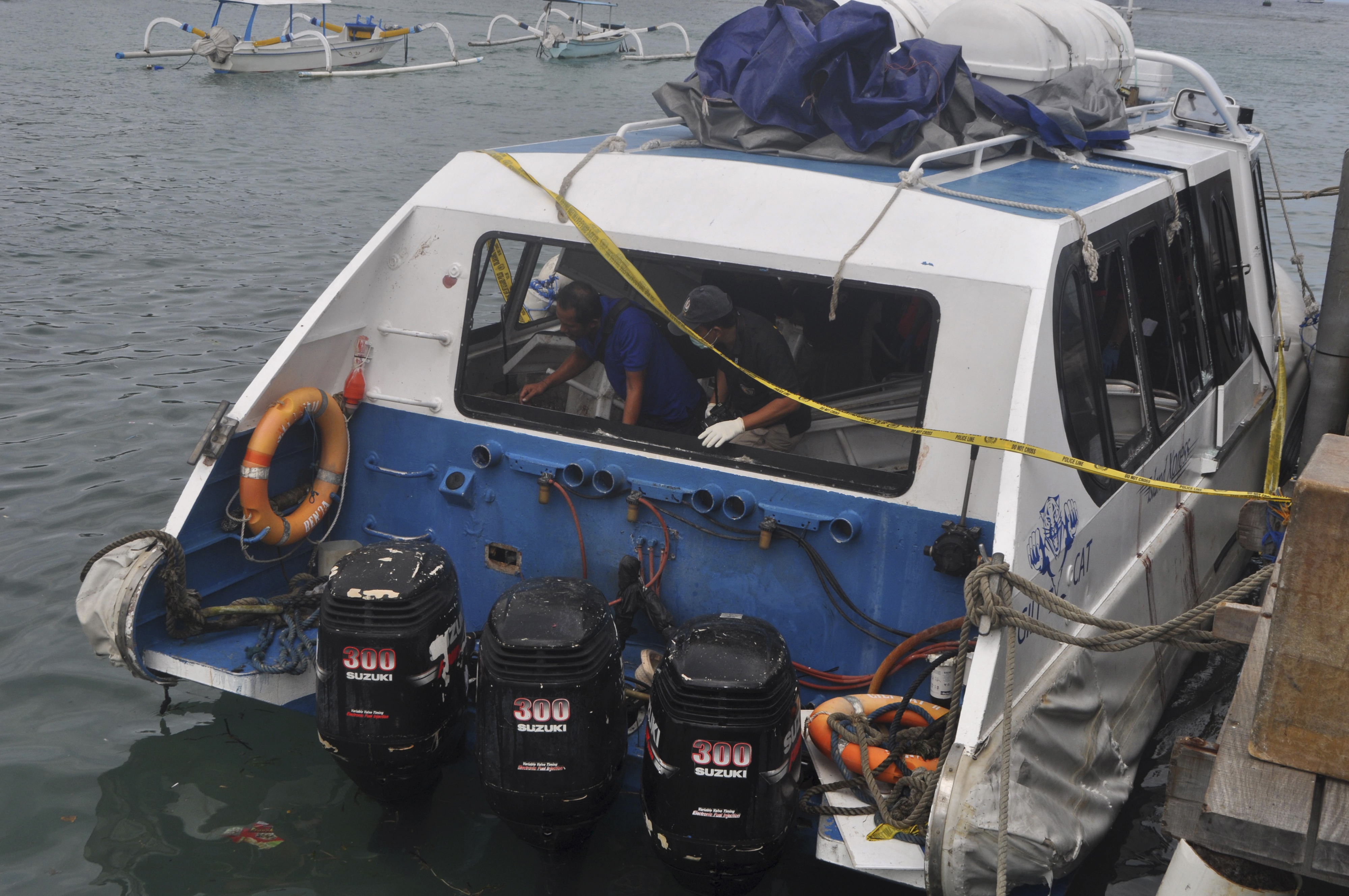 Police investigators examine the Gili Cat 2 boat following an explosion in Bali, Indonesia, Thursday, Sept. 15, 2016