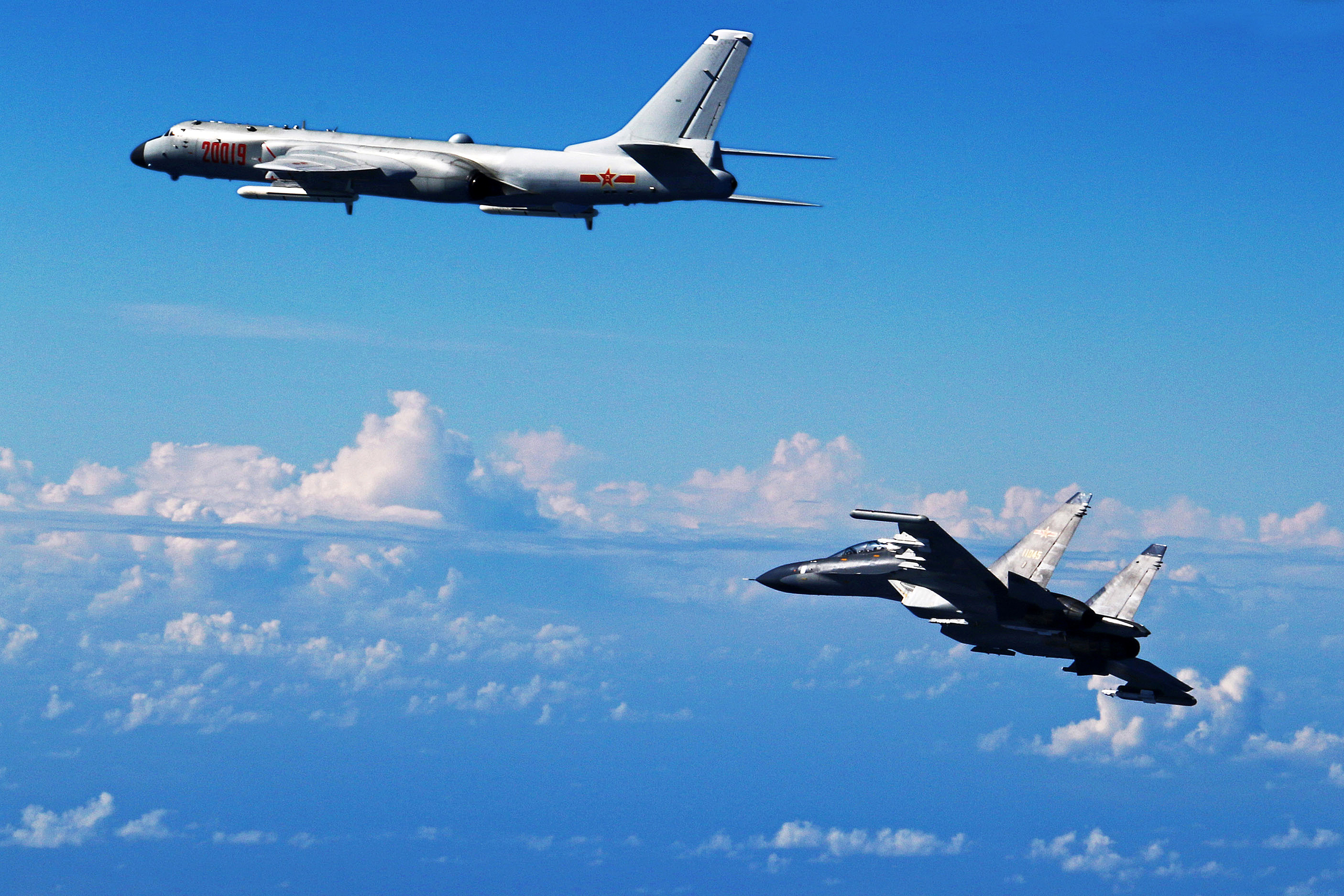 In this photo released by Xinhua News Agency, Chinese Air Force Su-30 fighter, right, flies along with a H-6K bomber as they take part in a drill near the East China Sea on Sept. 25, 2016