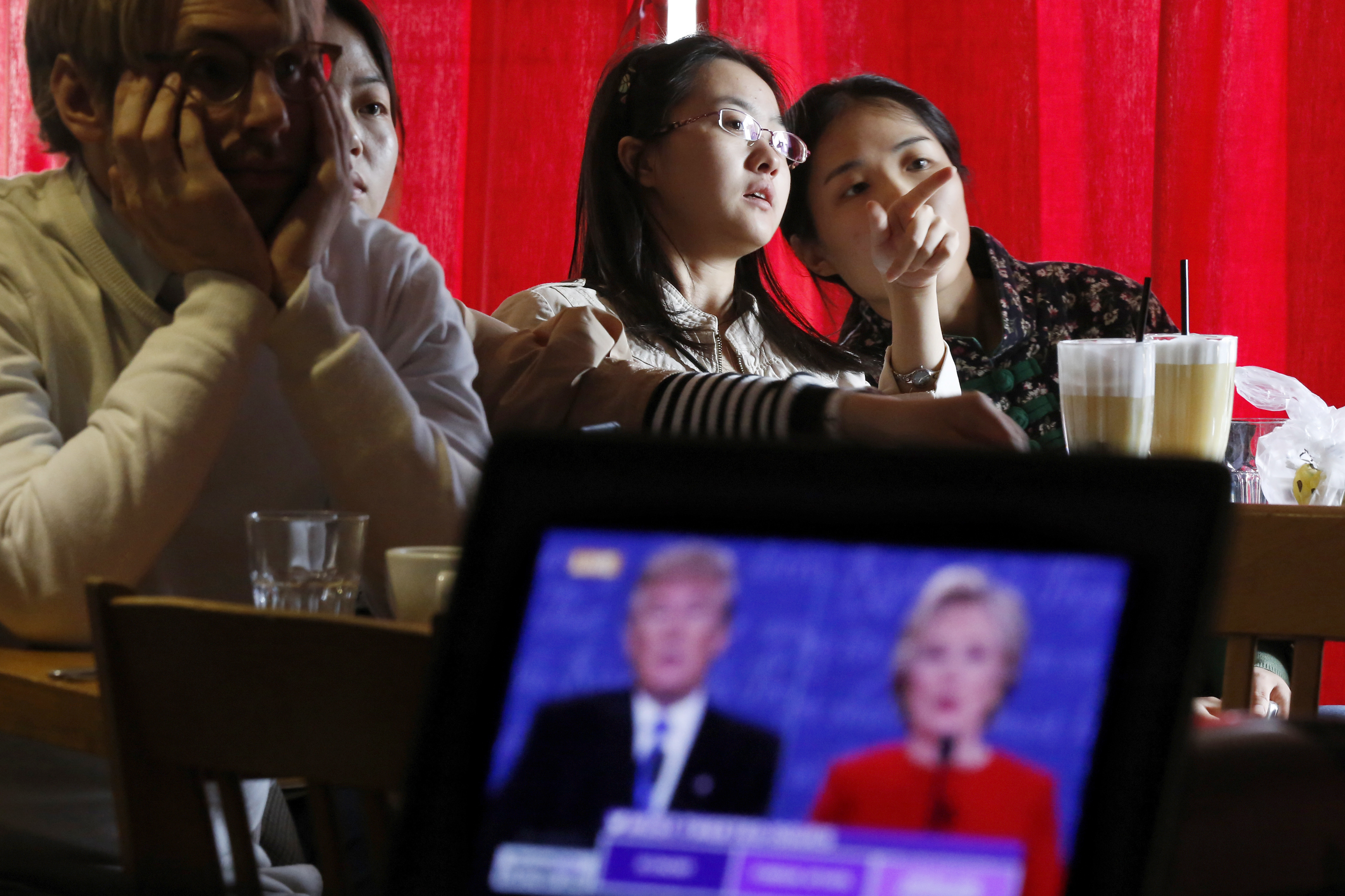 Chinese students chat as they watch a live broadcasting of the U.S. presidential debate at a cafe in Beijing on Sept. 27, 2016