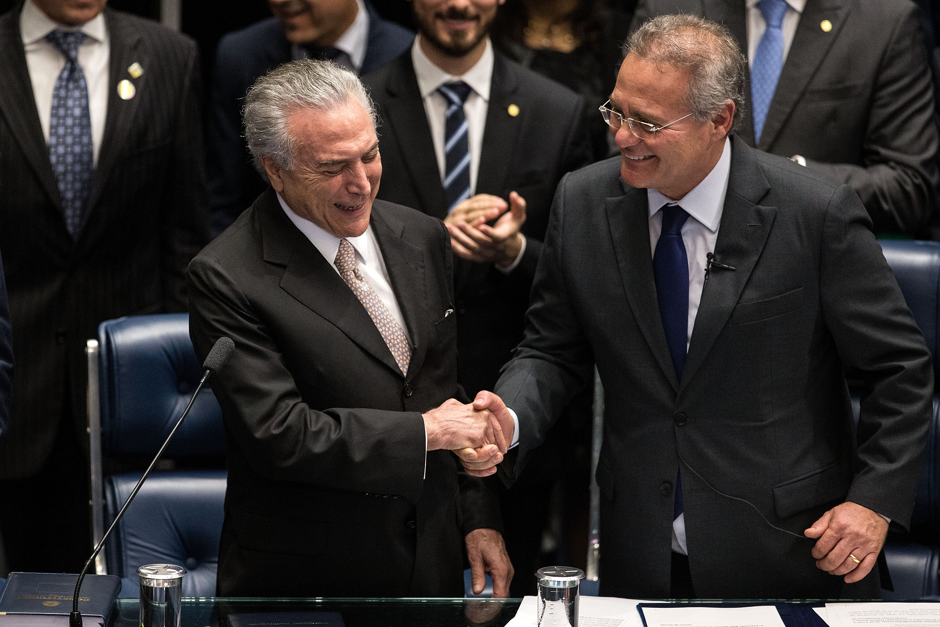 Michel Temer (L) shakes hands with Brazilian Senate President Renan Calheiros during his swear-in ceremony as President of Brazil in Brasilia, Brazil, Aug. 31, 2016.
