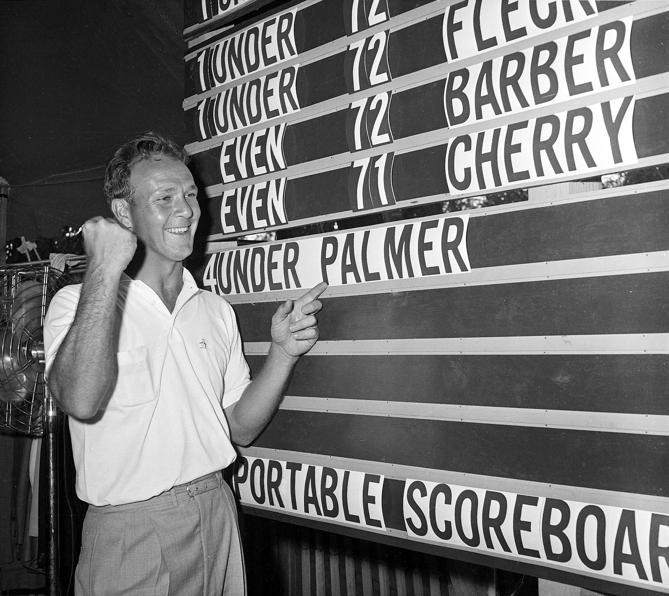 Arnold Palmer points to his name on the press tent scoreboard during the National Open golf tournament at the Cherry Hills Country Club in Denver June 19, 1960.