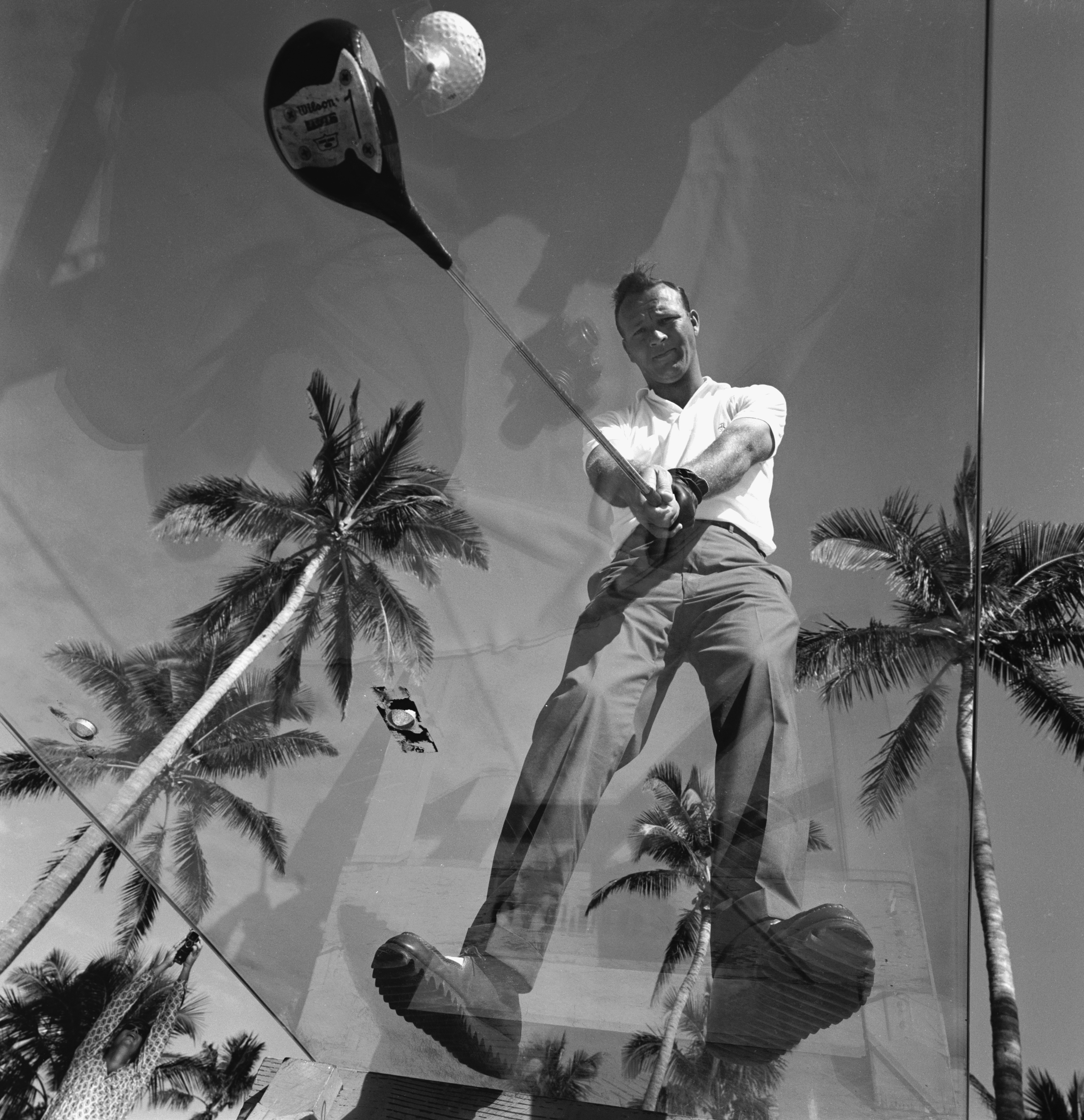Arnold Palmer stands on a sheet of glass and prepares to demonstrate his swing in Miami, in December 1960.