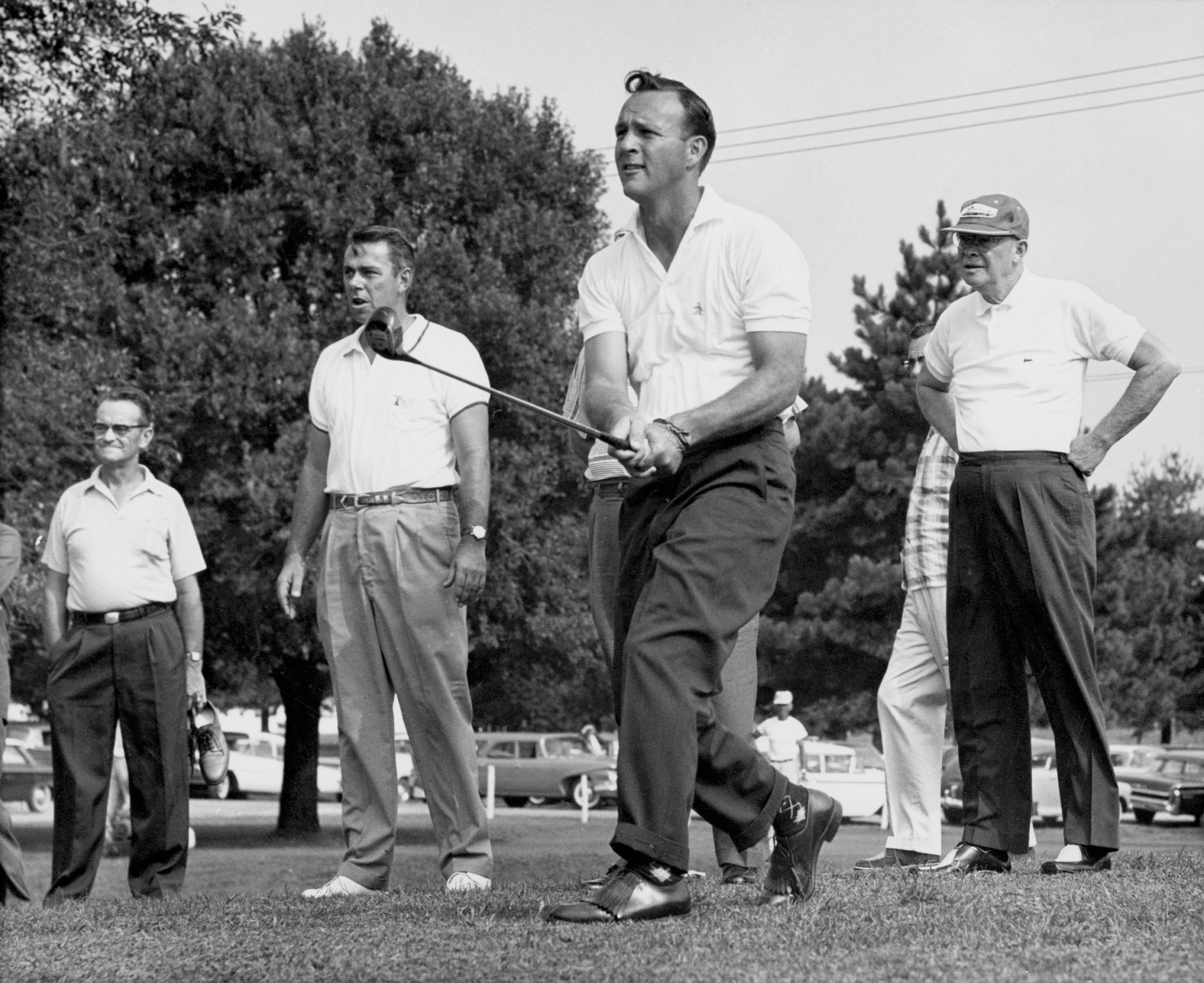 Arnold Palmer tees off as President Dwight D. Eisenhower watches.