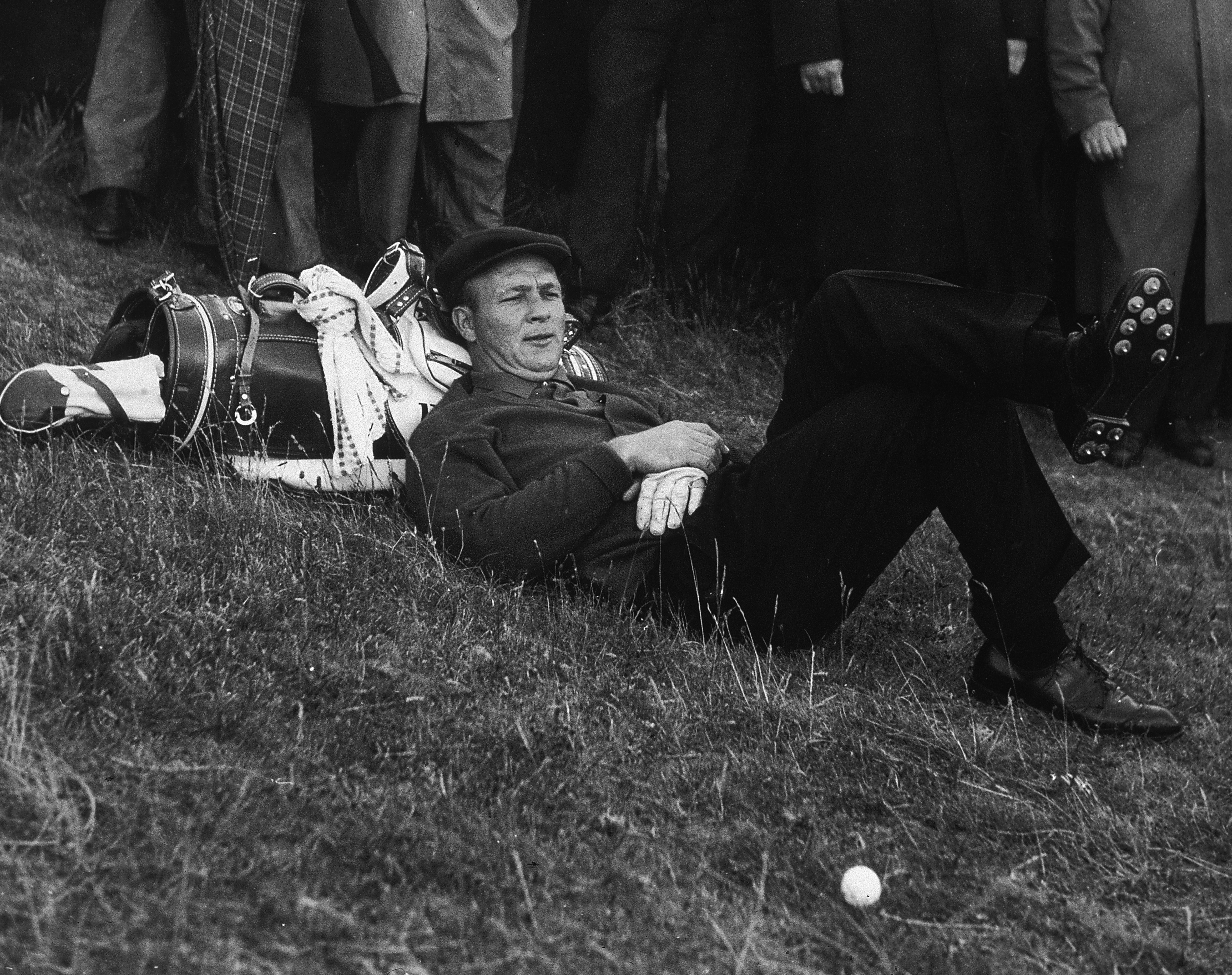 Arnold Palmer lays his head on his golf bag while taking a break between shots during a golf tournament in 1961.