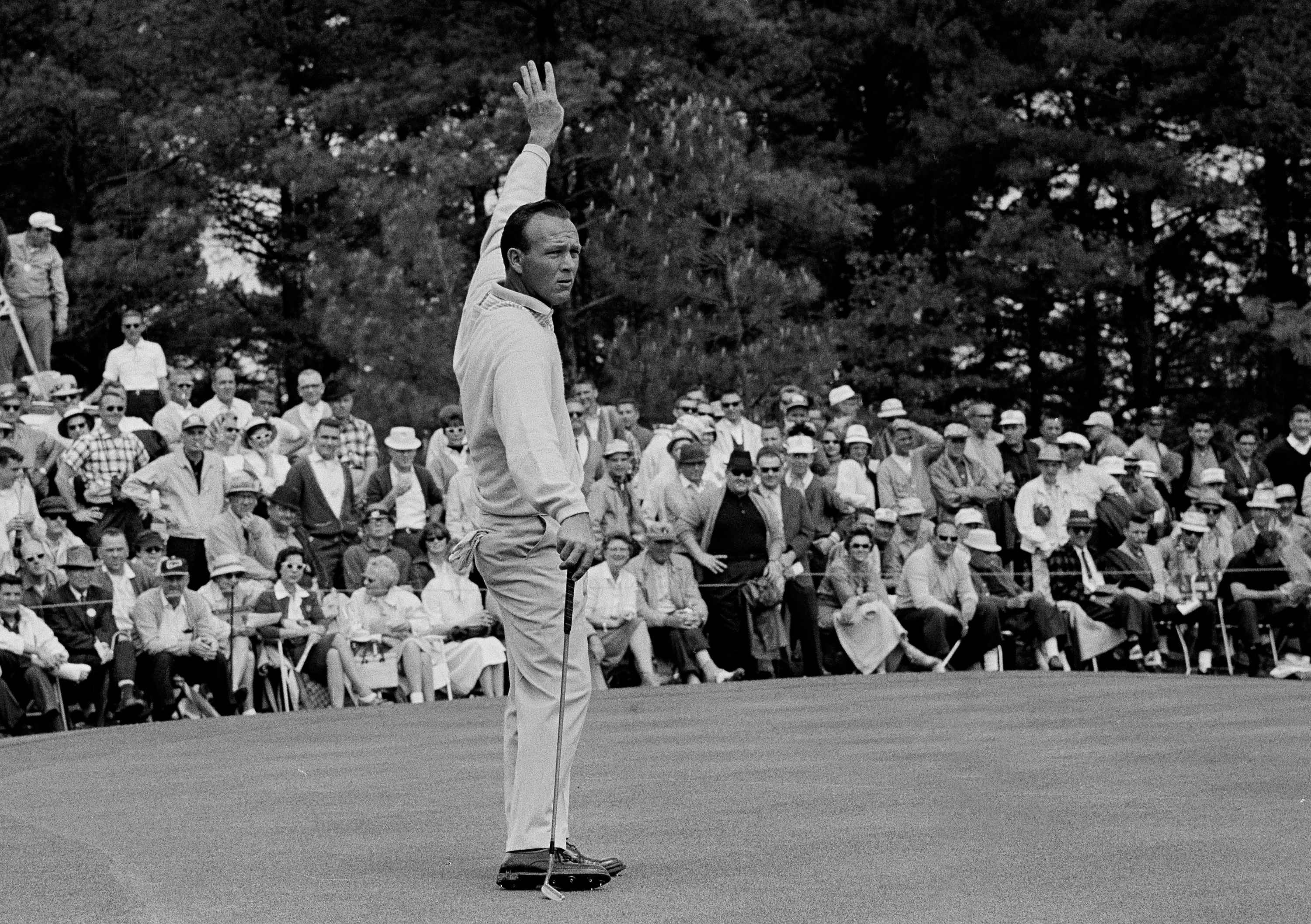 Arnold Palmer holds up his hand to quiet the crowd during the Masters Golf Tournament in Augusta, Ga. April 7, 1963.