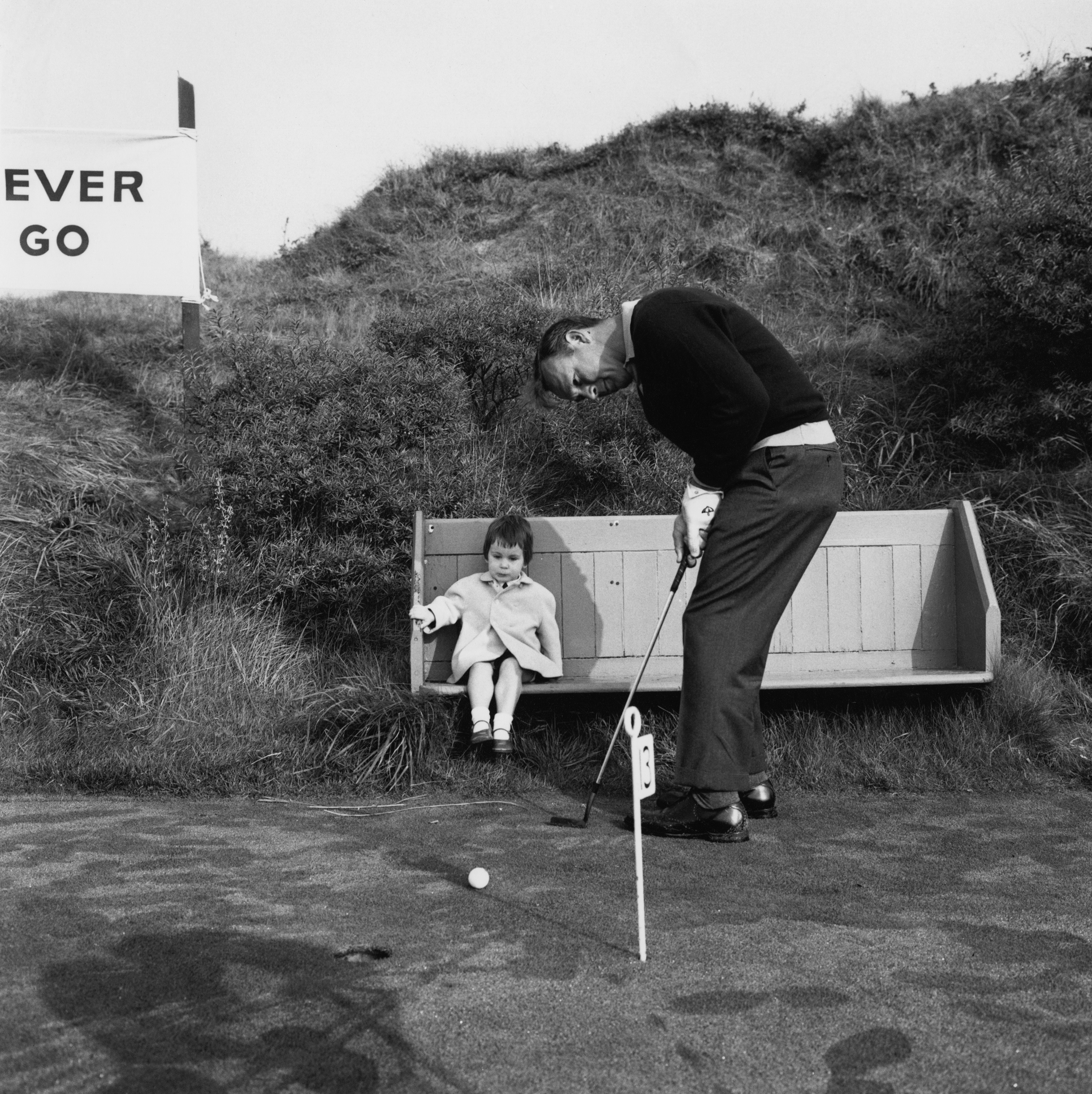 Arnold Palmer shows young Jane Coop how to putt at Royal Birkdale, Southport, where he was practicing for his Ryder Cup match on October 7, 1965.