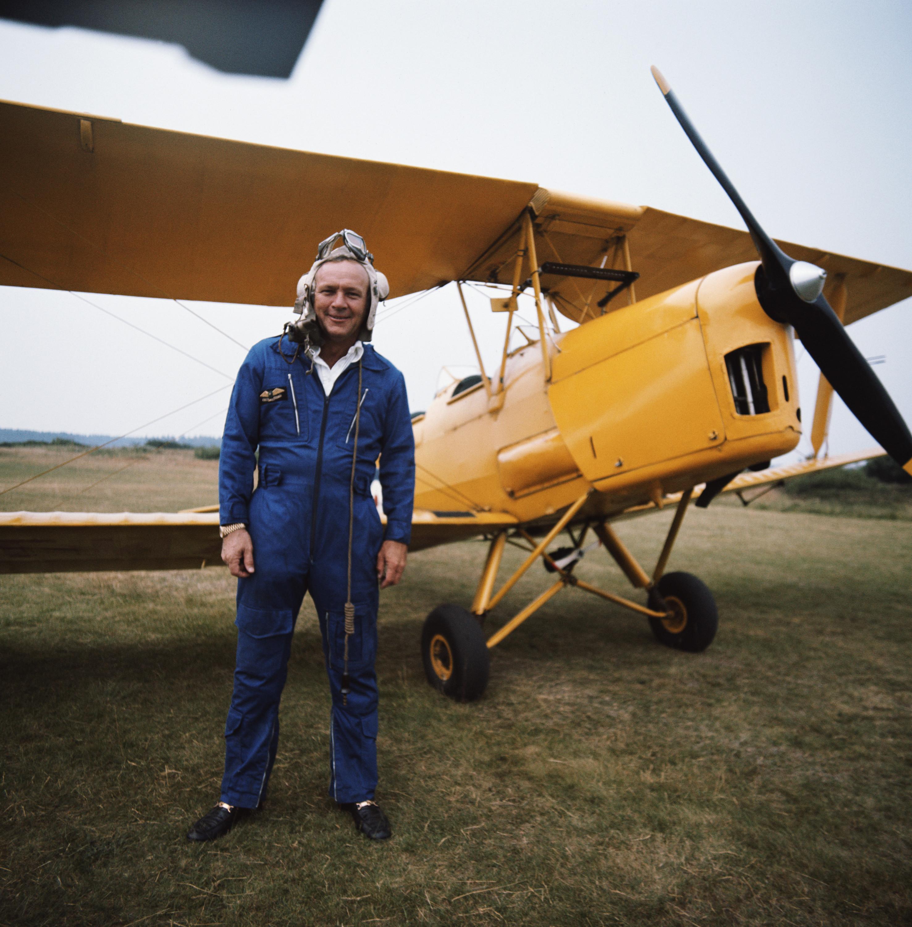 Arnold Palmer stands next to a bi-plane.