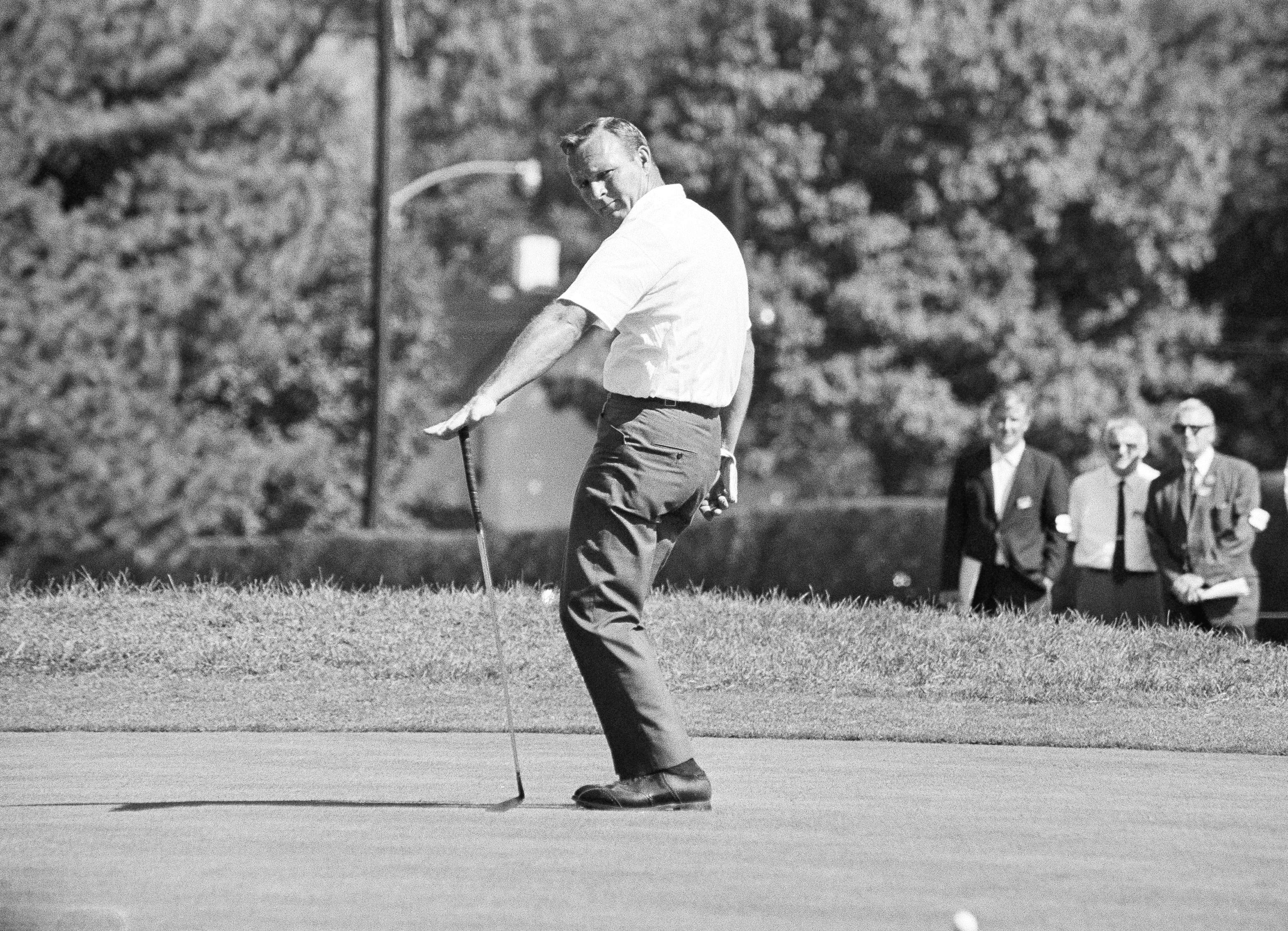 Arnold Palmer does a little balancing act with his putter as he urges a ball that failed to drop in the hole on the 6th green in first round of the Philadelphia Golf Classic on Sept. 15, 1967 at Whitemarsh Valley Country Club in Laurel Valley, Pa.