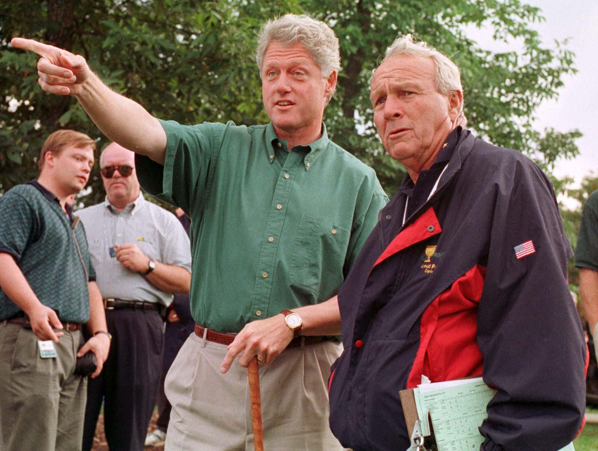1996 President Bill Clinton and golfing legend Arnold Palmer check out the action during the opening round of the Presidents Cup in Manassas, Sept. 13, 1996.