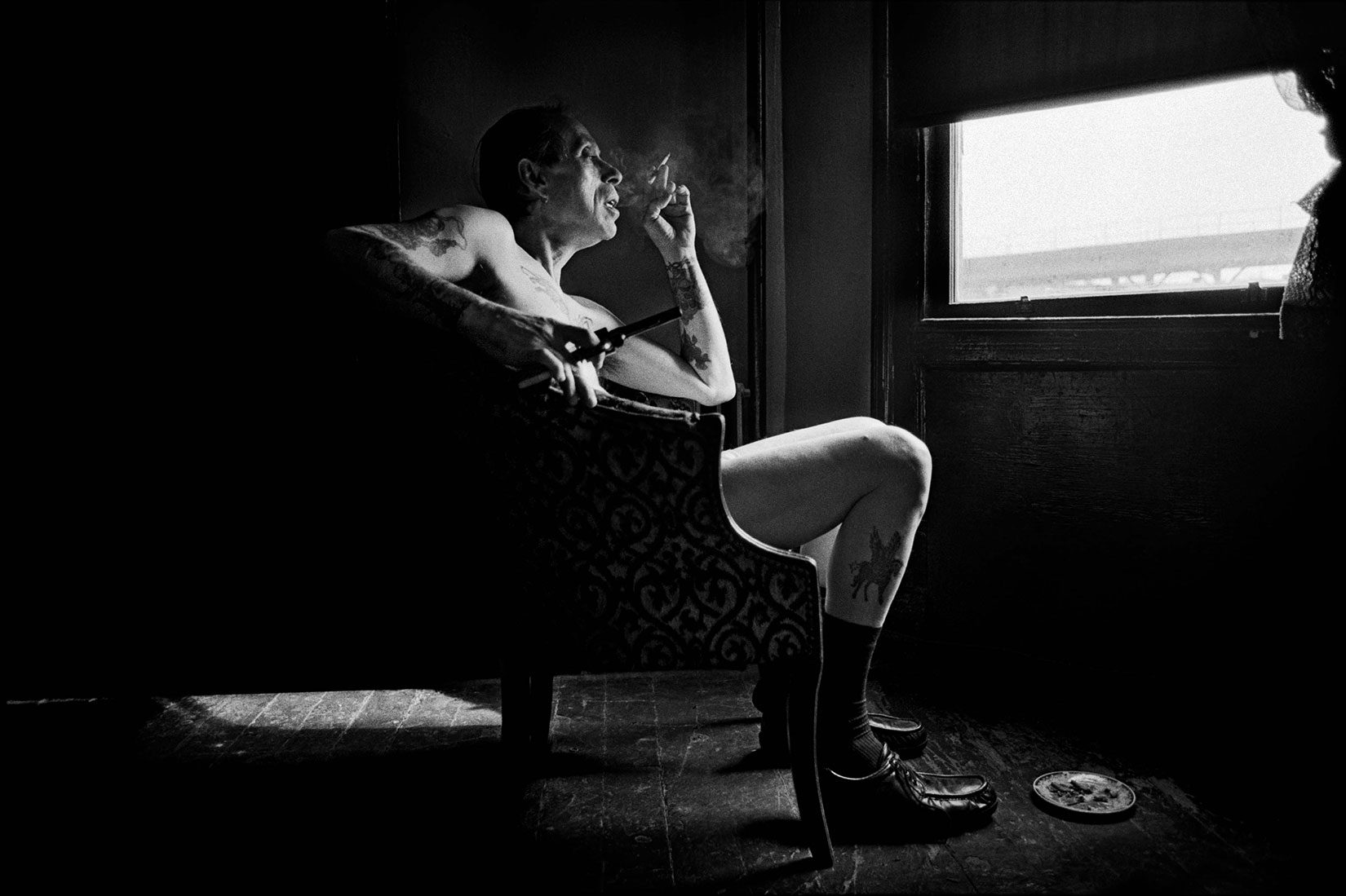 The Sol Mednick Gallery, Pa.: Sept. 30 - Oct. 28                                                                                             (Caption: Uncle Charlie contemplating in his living room the reality that his son Joe is dying from HIV, sitting by the window holding his newest and latest handgun in his apartment in Bushwick, Brooklyn in 1996)