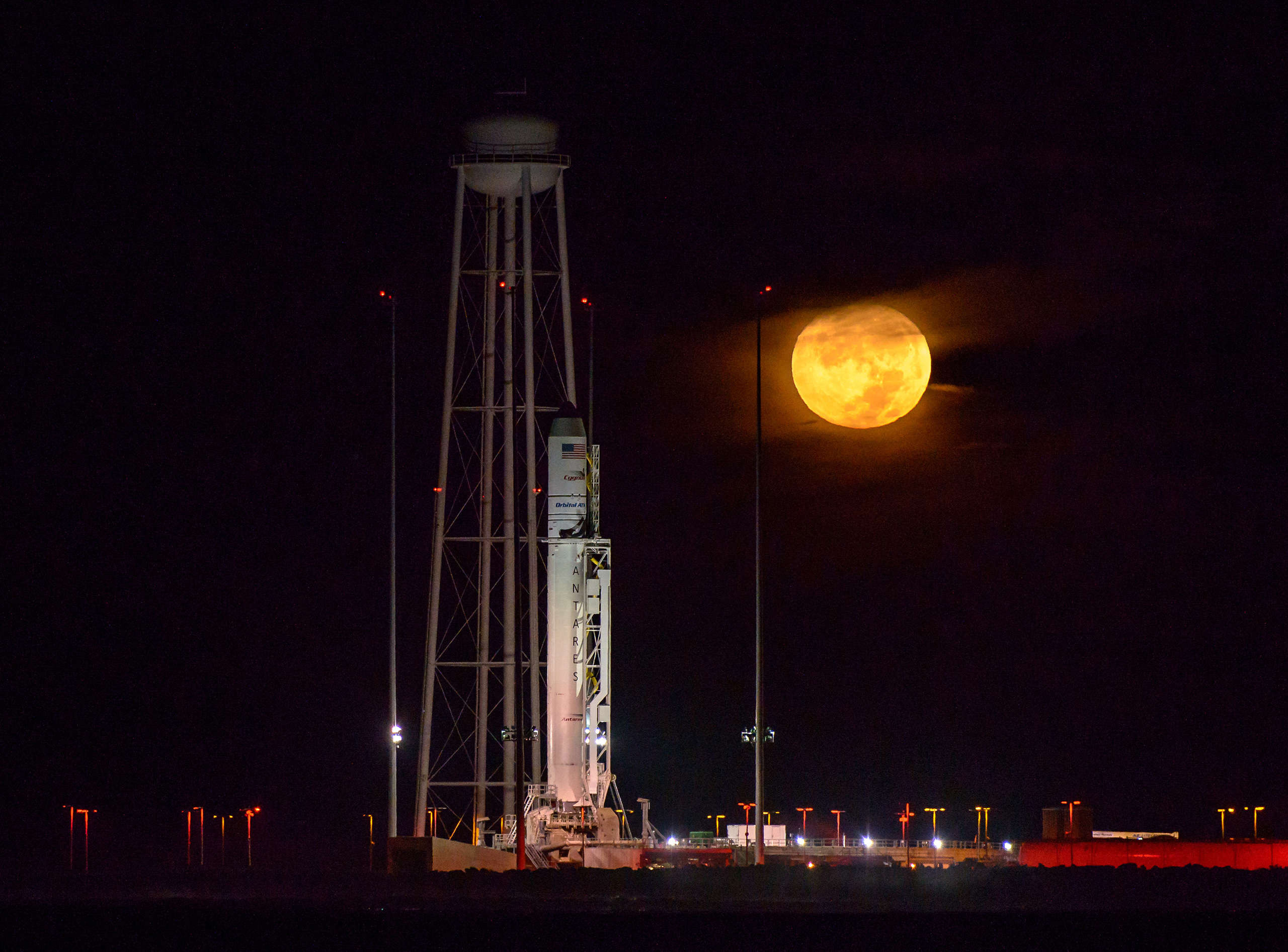 The Orbital ATK Antares rocket, with the Cygnus spacecraft onboard, is seen on launch Pad-0A as the moon sets, predawn,  at NASA's Wallops Flight Facility in Virginia, on Oct. 15, 2016.