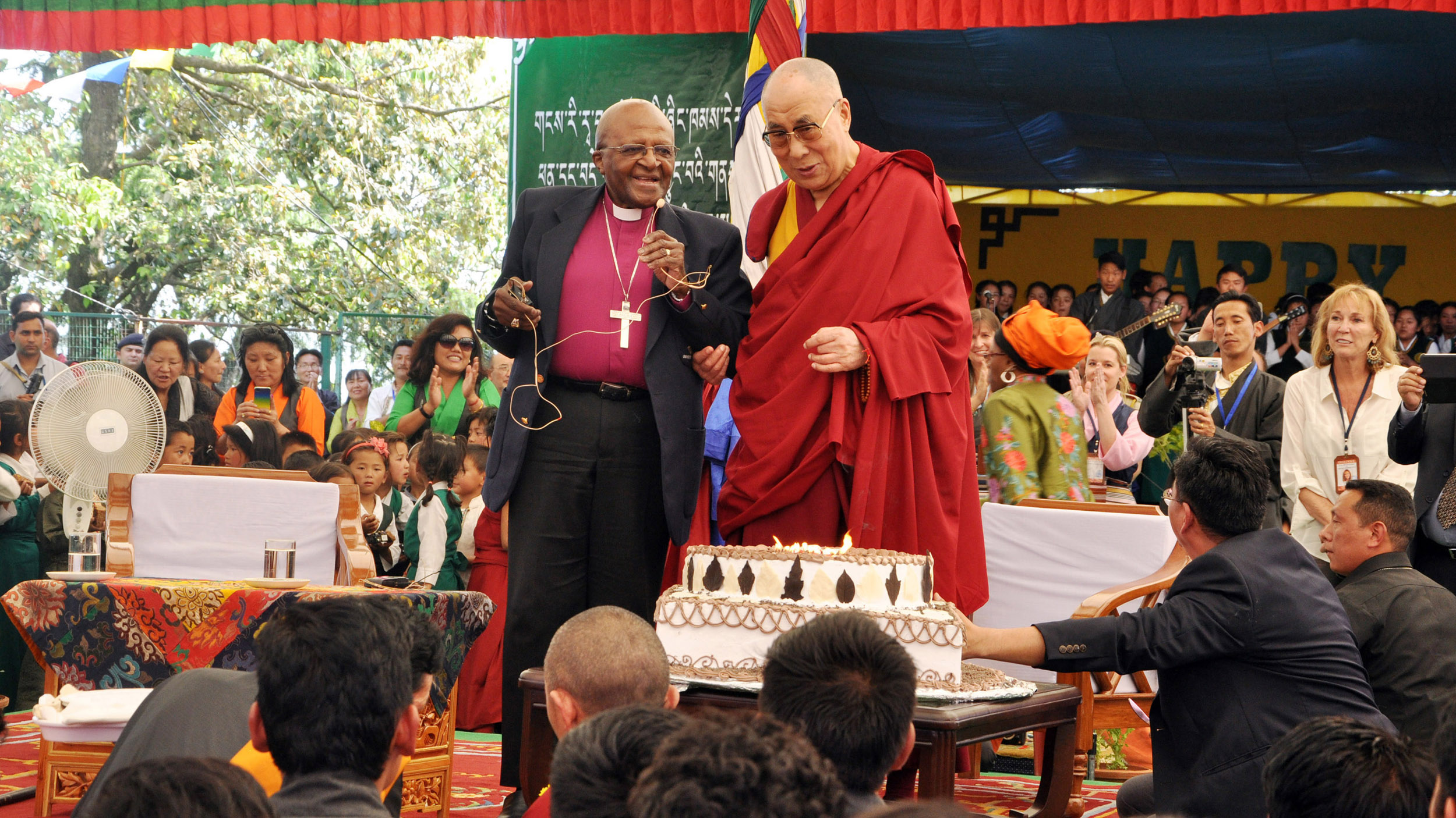 Spiritual leader Dalai Lama to blow out candles on his birthday cake as retired Archbishop Desmond Tutu looks on at the Tibetan Childrens Village School in Dharmsala, India, on April 23, 2015.