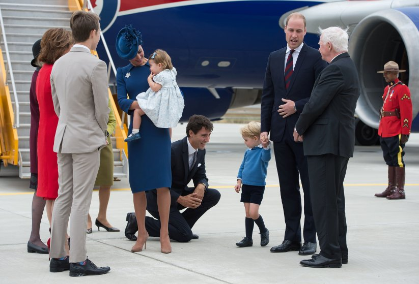 Canadian Prime Minister Justin Trudeau kneels to talk to Prince George as his father Prince William, The Duke of Cambridge, speaks with the Governor General David Johnston and Catherine, The Duchess of Cambridge, holds their daughter Princess Charlotte upon arrival at 443 Maritime Helicopter Squadron base on in Victoria, British Columbia, Sept. 24, 2016.
