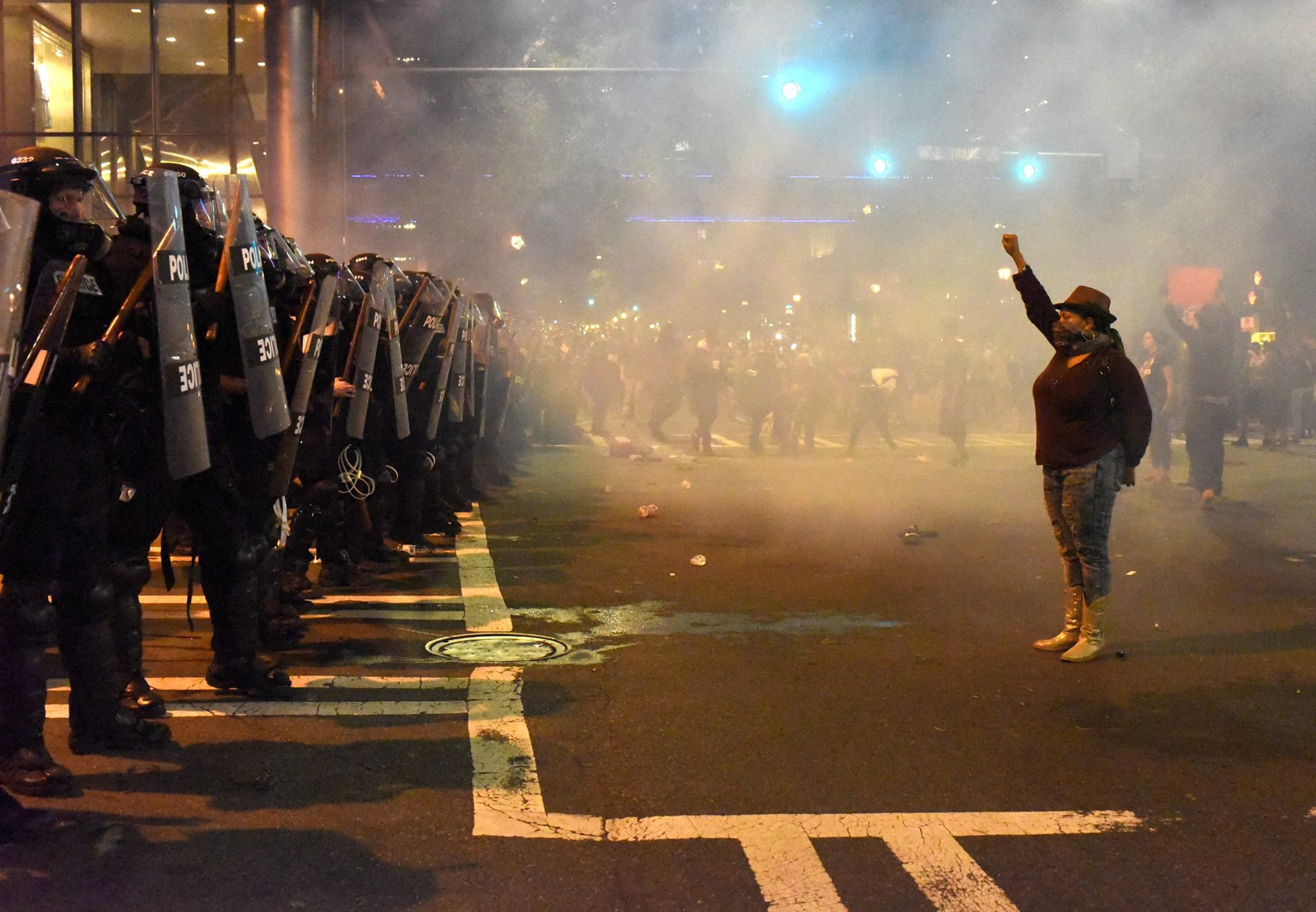 A protester raises her fist as she confronts police officers in Charlotte, N.C., on Sept. 21, 2016. Police and protesters clashed following the fatal police shooting of Keith L. Scott,  a black man.