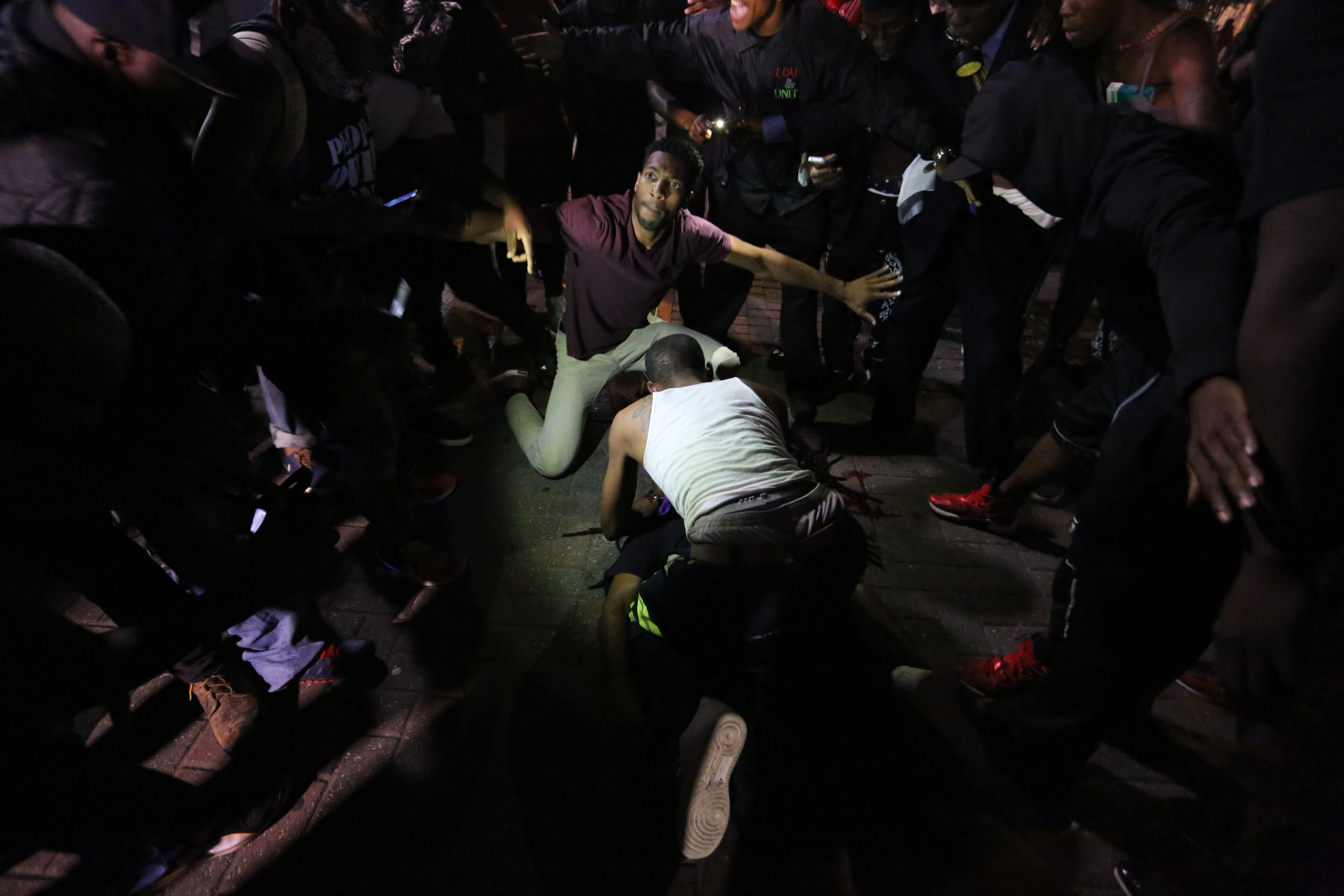 A young man is attended to as he lies on the sidewalk after being shot in front of the Omni Hotel in downtown Charlotte, N.C., Sept. 21, 2016.