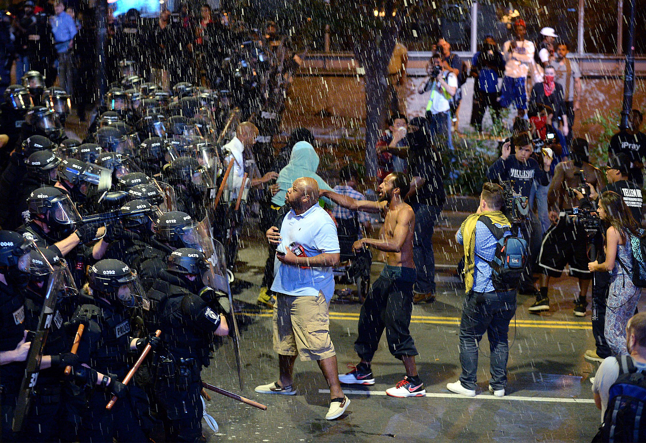 Debris falls upon police officers and protesters as officers began to push protesters from the intersection in Charlotte, N.C. on Sept. 21, 2016.