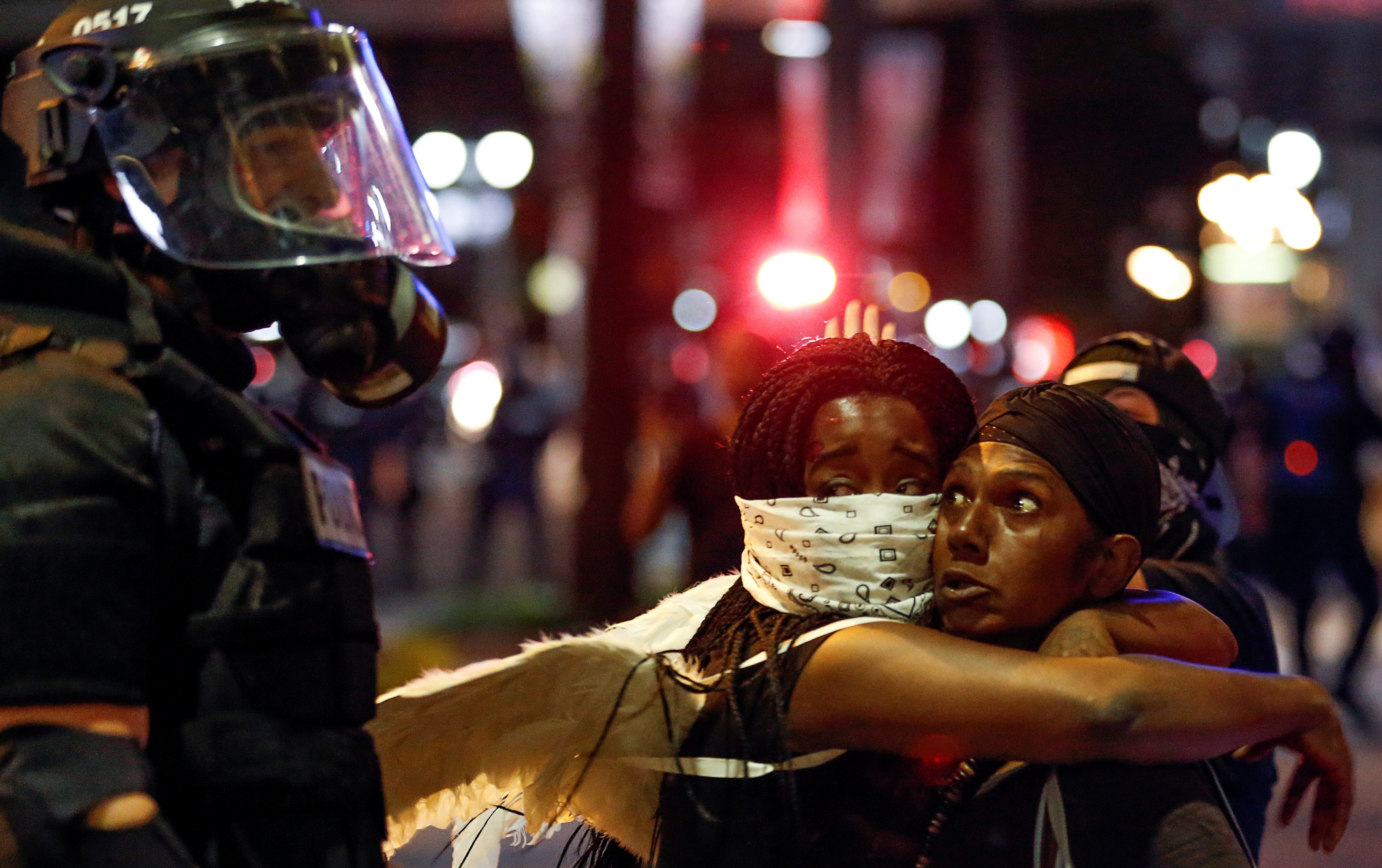Two women embrace while looking at a police officer in uptown Charlotte, N.C. during a protest of the police shooting of Keith Scott on Sept. 21, 2016.