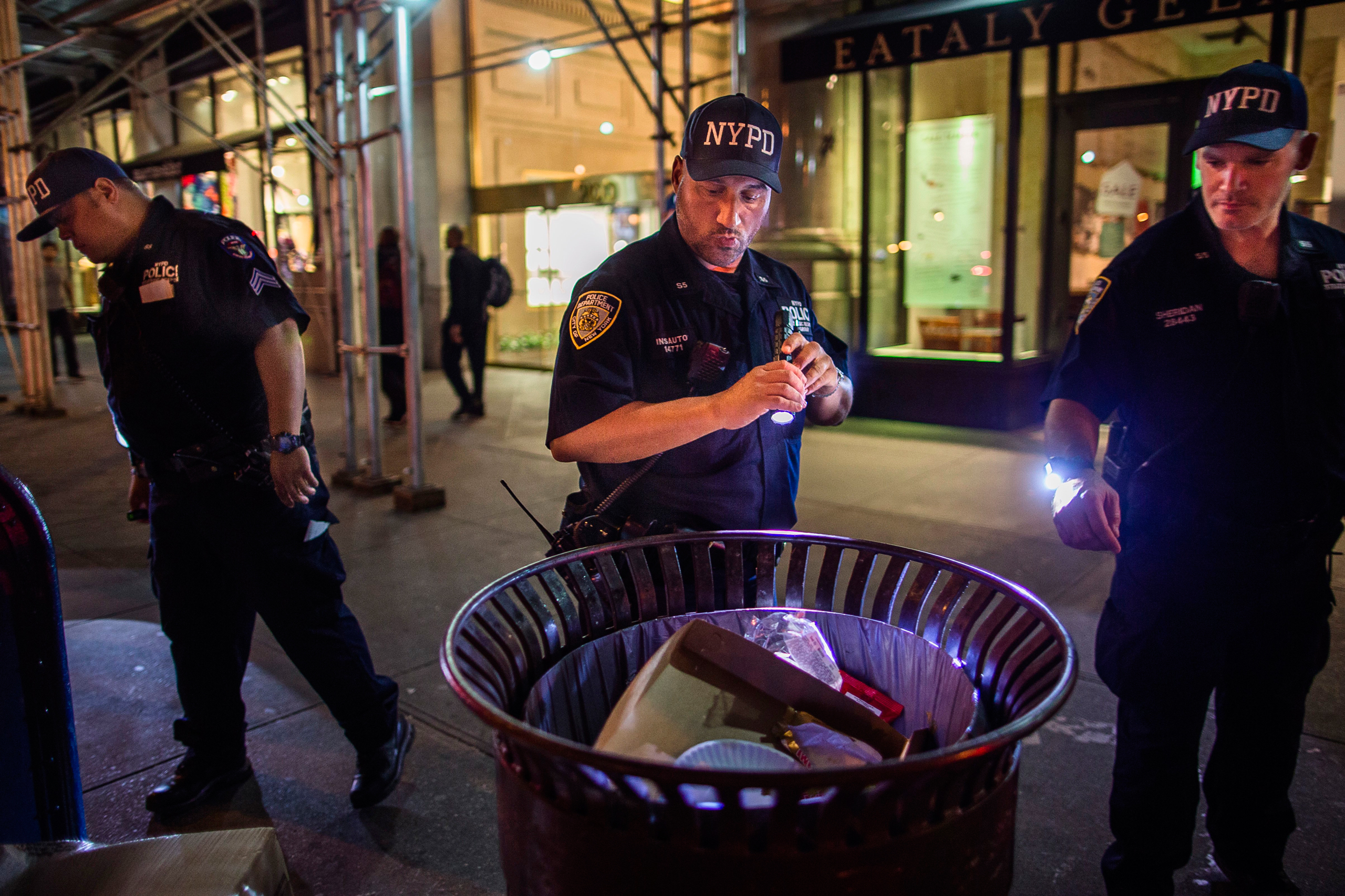Police officers look for suspicious packages along Fifth Avenue near the scene of an explosion on West 23rd Street and 6th Avenue in Manhattan's Chelsea neighborhood in New York in the early hours of Sept. 18, 2016.