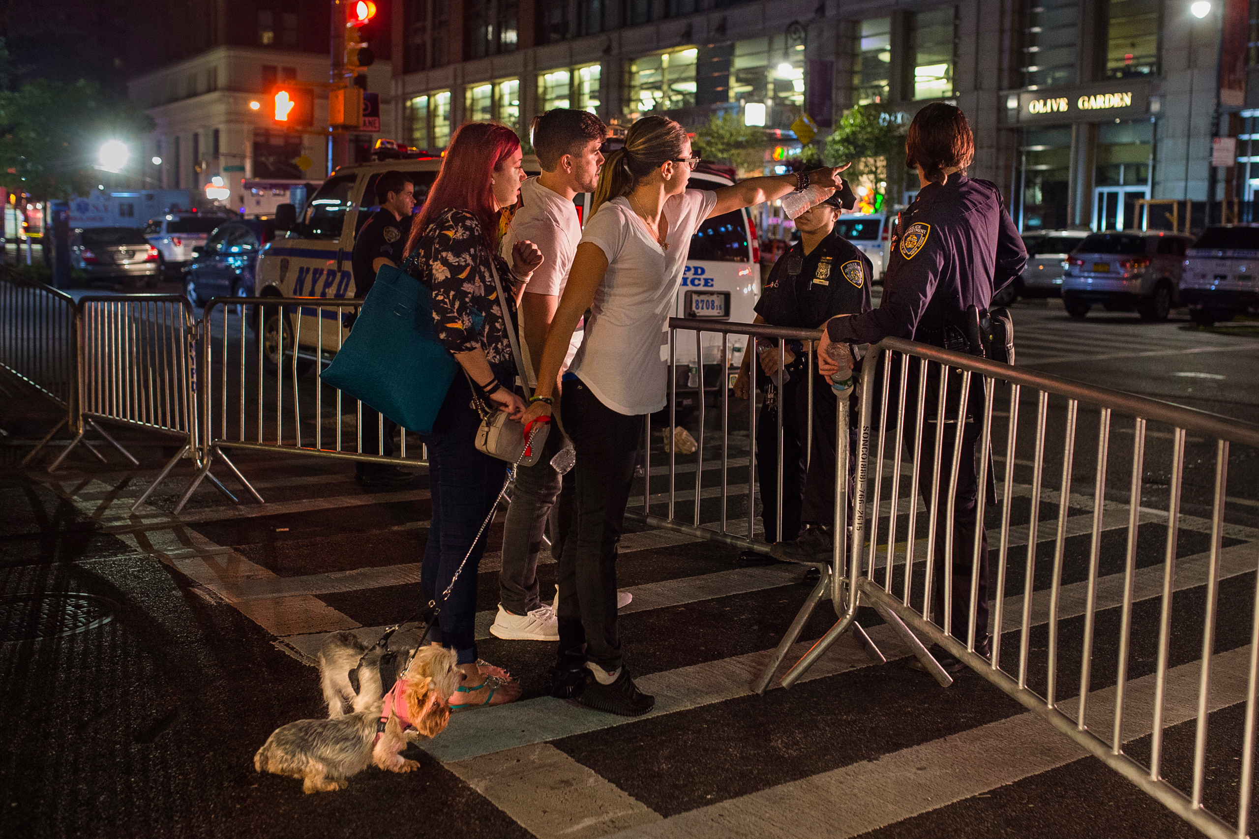 People try to access the area near the scene of an explosion on West 23rd Street and 6th Avenue in Manhattan's Chelsea neighborhood, in New York, early Sunday, Sept. 18, 2016. An explosion rocked the block of West 23rd Street between Sixth and Seventh Avenues at 8:30 p.m. Saturday. Officials said more than two dozen people were injured. Most of the injuries were minor. (AP Photo/Andres Kudacki)