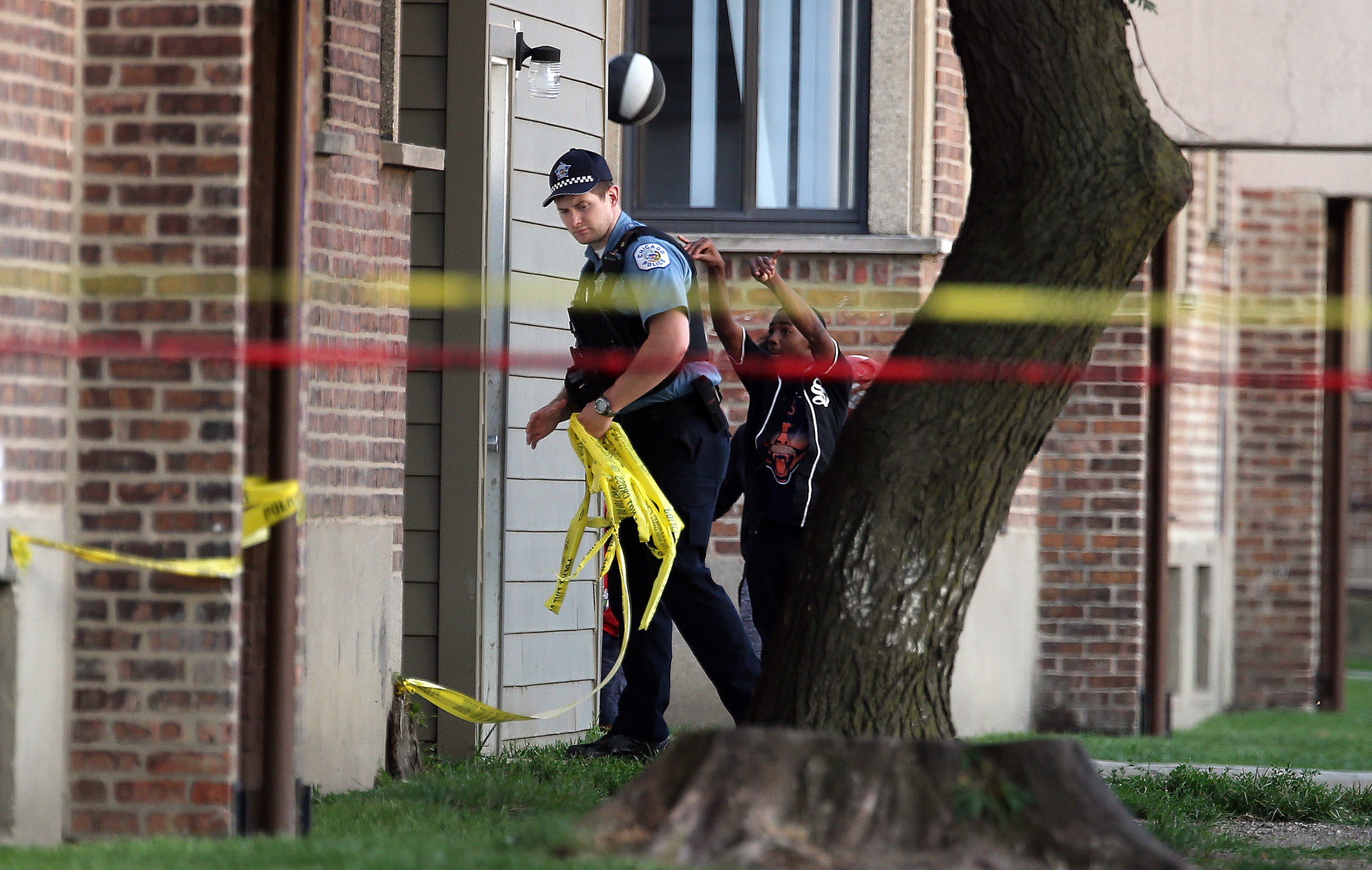 Kids play basketball as Chicago Police remove crime scene tape after a fatal shooting on Calumet Avenue south of 63rd Street on Aug. 26, 2016.