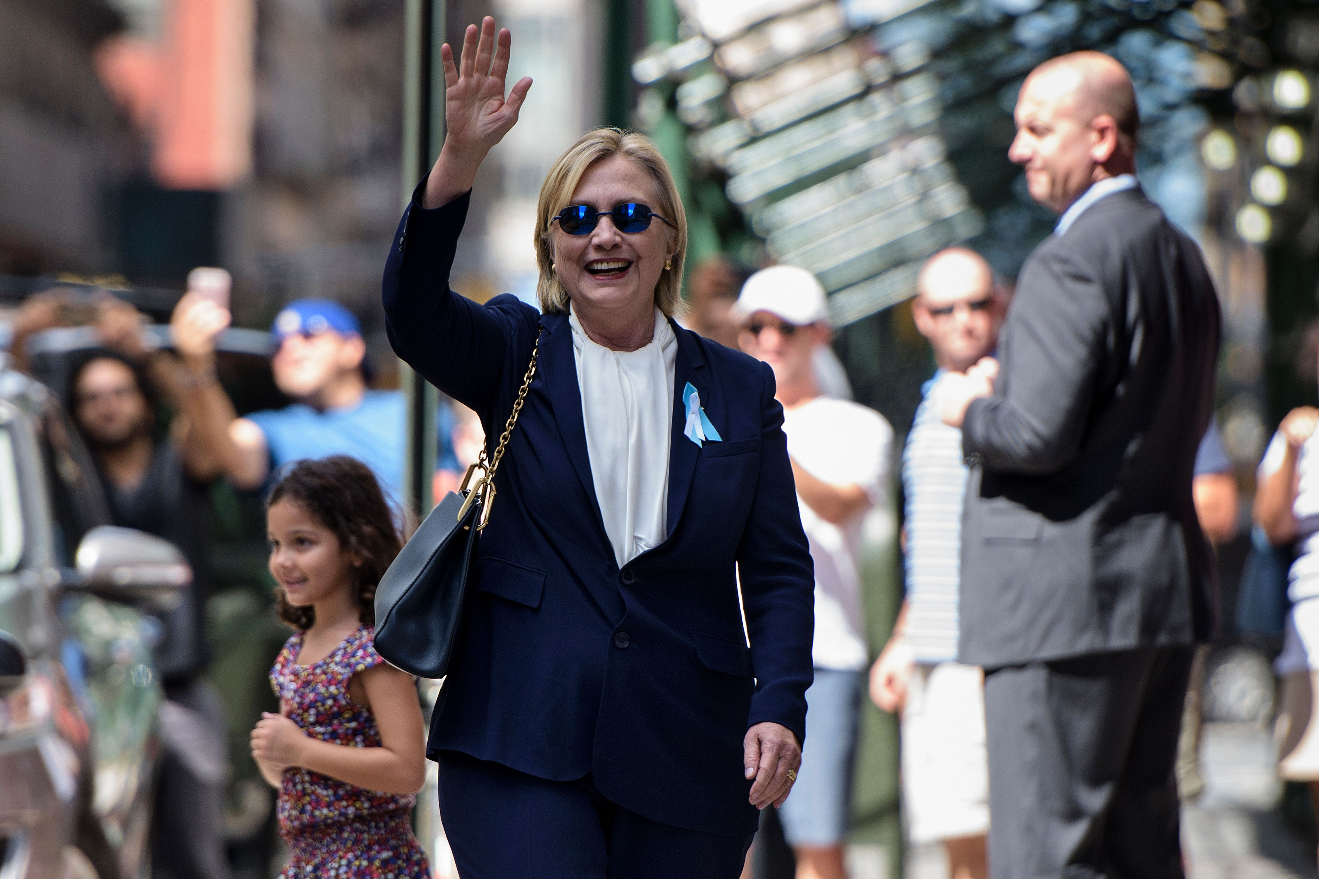 Democratic presidential nominee Hillary Clinton waves to the press as she leaves her daughter's apartment building after resting in New York on  on Sept. 11, 2016.