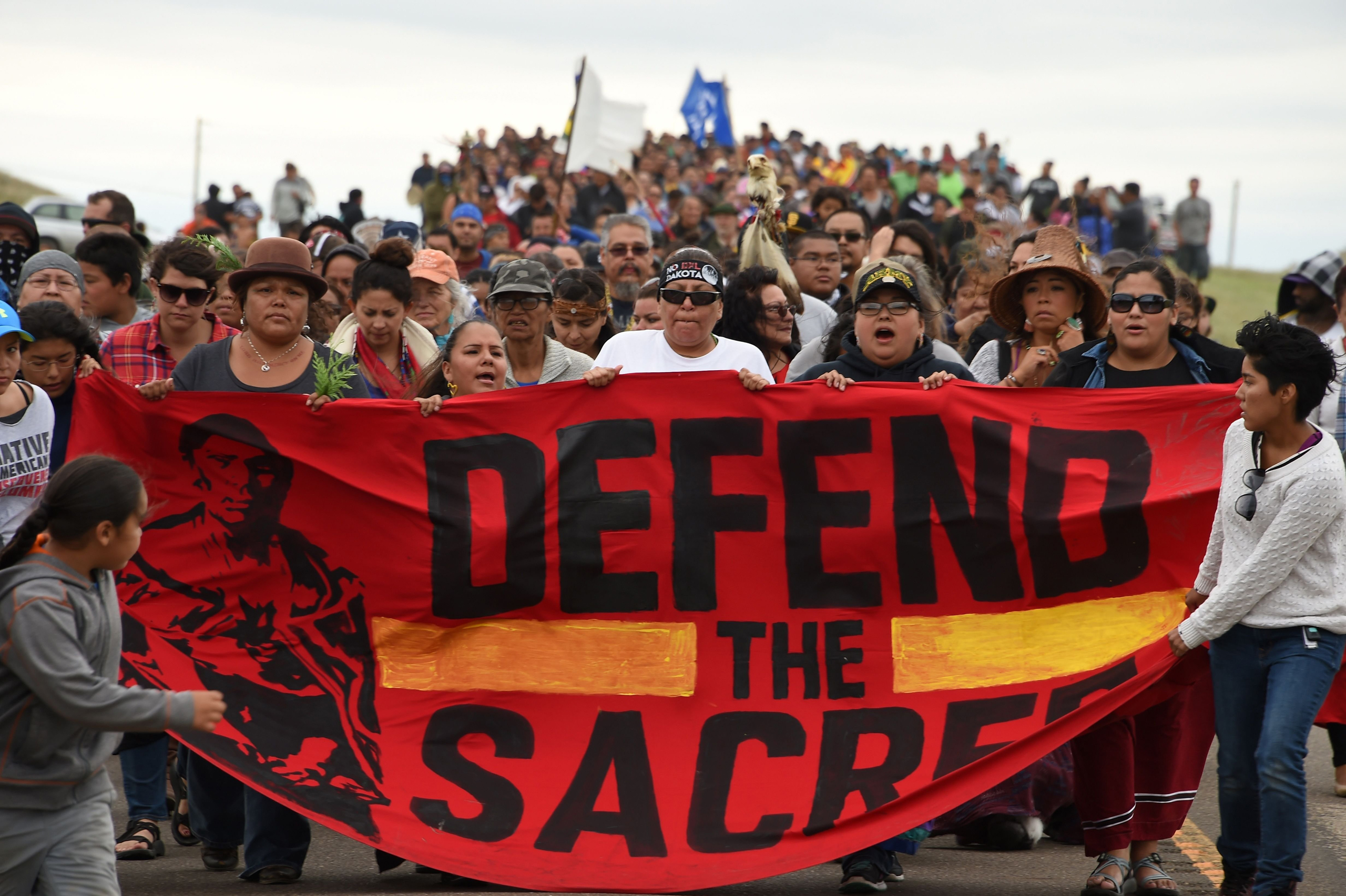 Native Americans march to a sacred burial ground site that was disturbed by bulldozers building the Dakota Access Pipeline (DAPL), near the encampment where hundreds of people gathered to join the Standing Rock Sioux Tribe's protest of the oil pipeline that is slated to cross the Missouri River near Cannon Ball, North Dakota, Sept. 4, 2016.