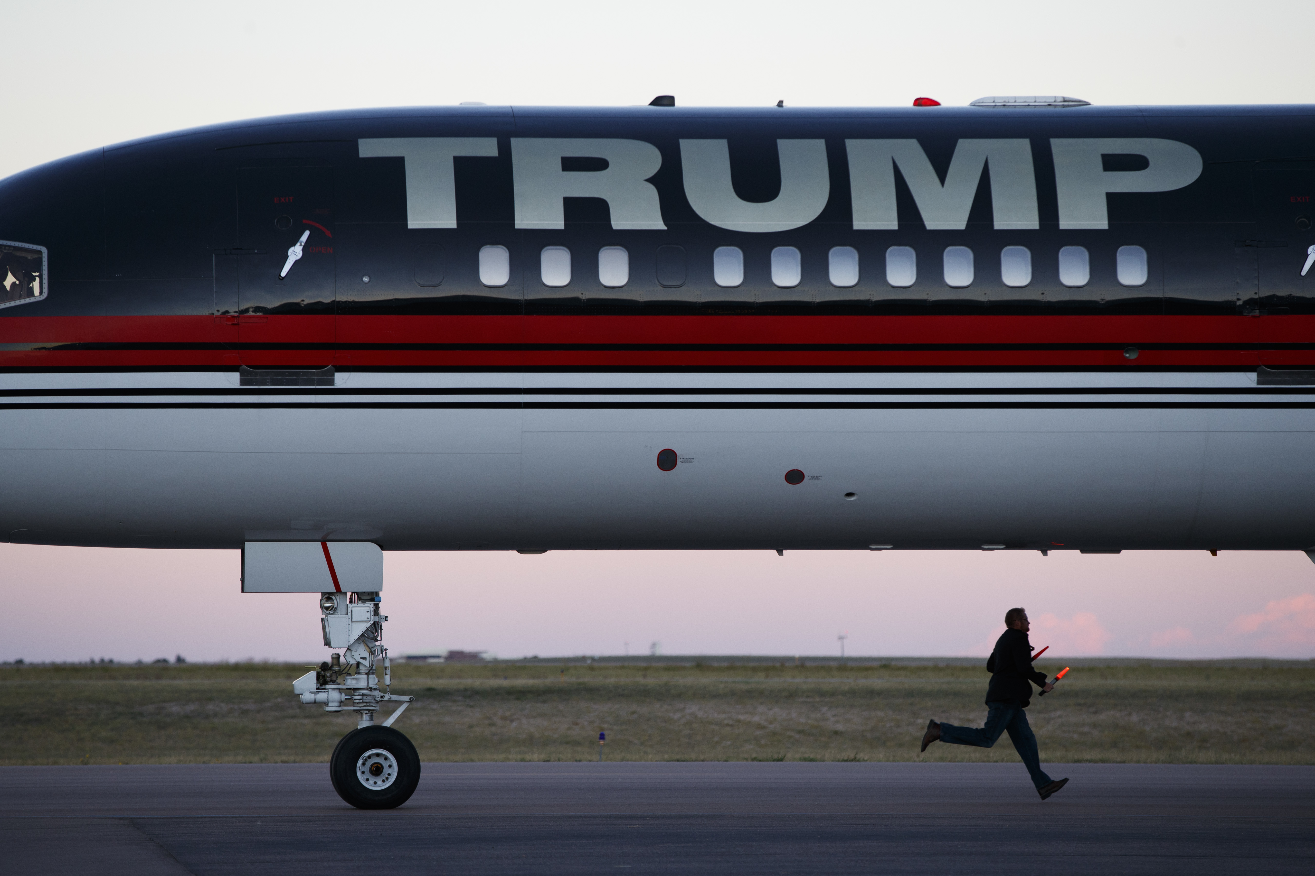 An airport worker races to prepare the stairs as the plane of Republican presidential candidate Donald Trump arrives for a campaign rally on Sept. 17, 2016, in Colorado Springs, Colo.