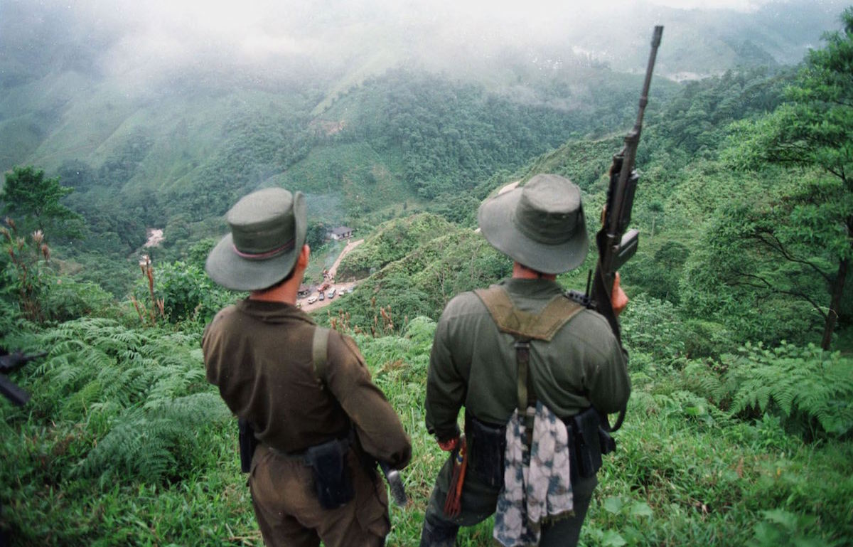 Two armed soldiers belonging to the Revolutionry Armed Forces of Colombia (FARC) monitor the Berlin pass, in Colombia in 1998.
