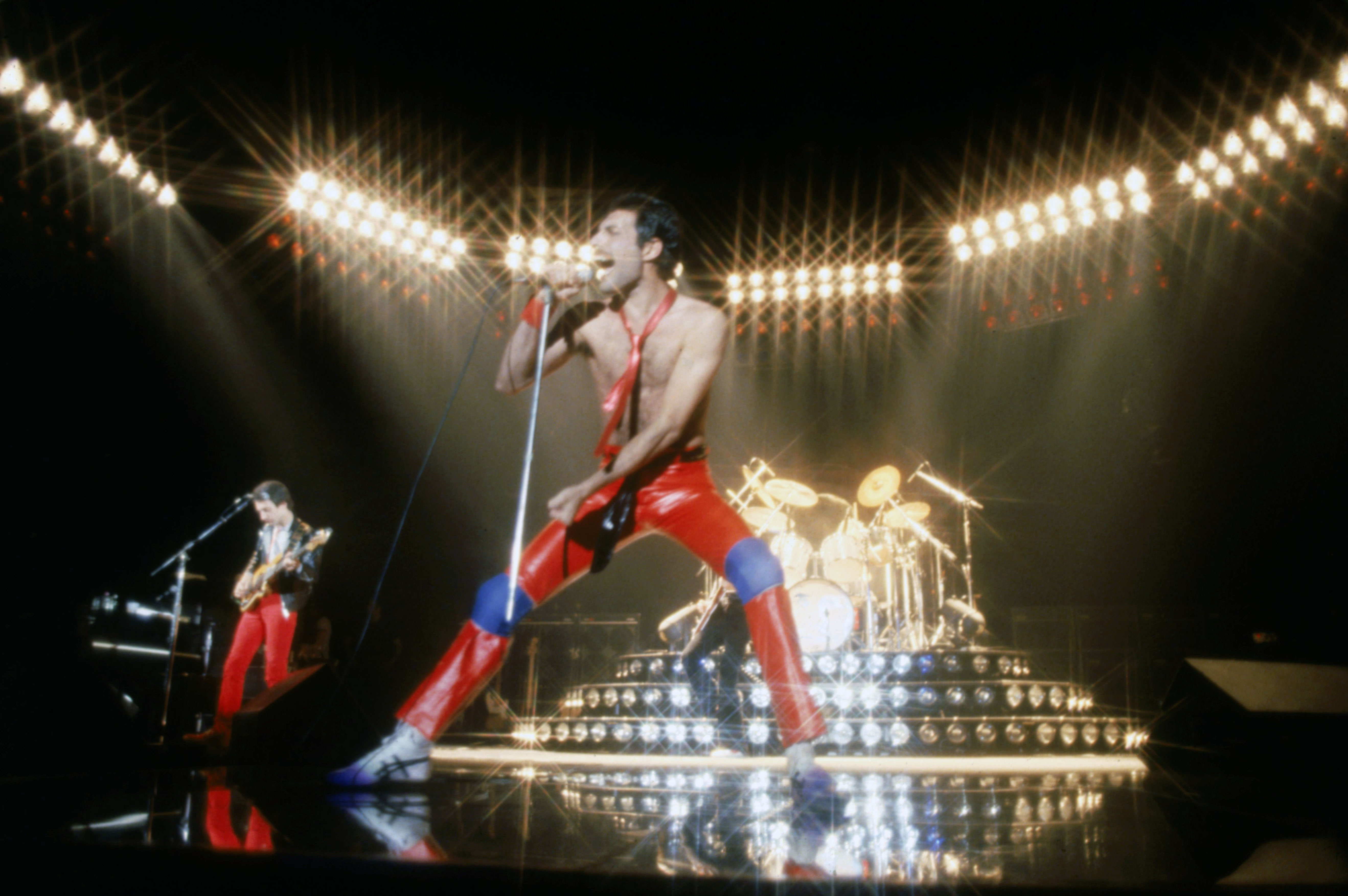 Musician John Deacon and Freddie Mercury  (C)(1946 - 1991) of British rock band Queen in concert, 1980.