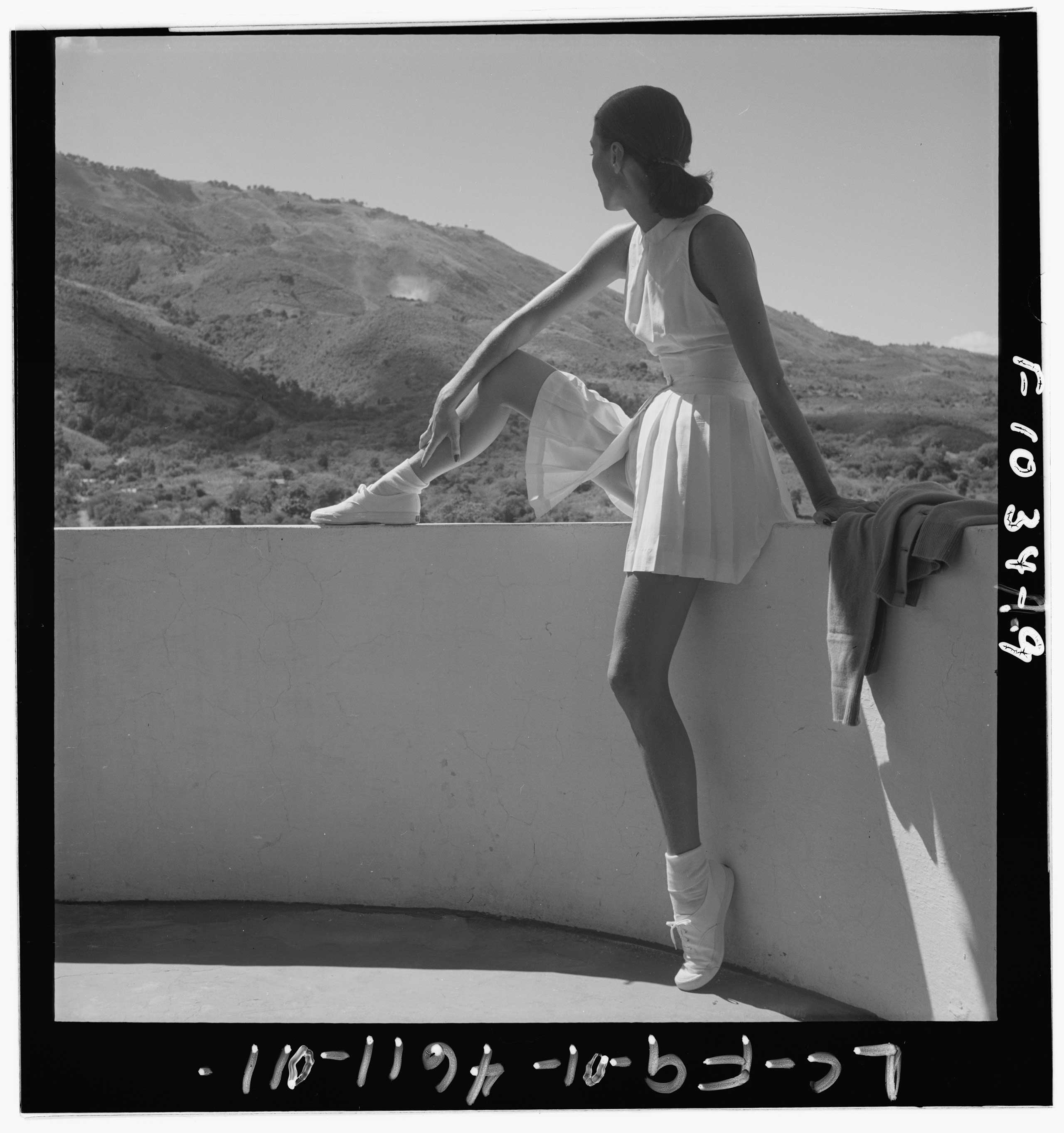 Woman wearing tennis outfit, seated on wall, with one leg on top of wall, looking at the mountains behind her. Published in Harpers Bazaar, Feb. 1947.
