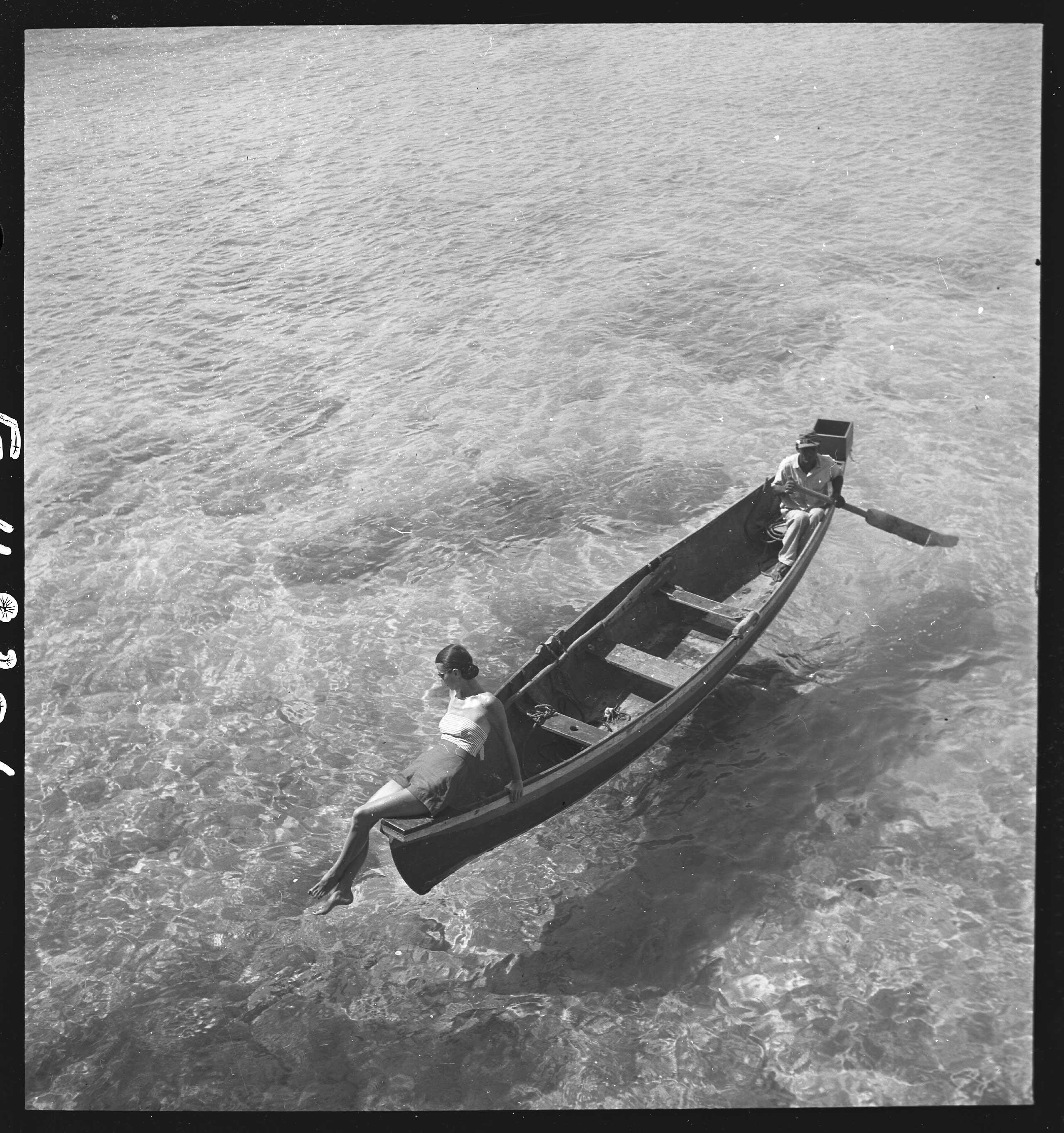 Fashion model on edge of boat, man rowing, Montego Bay, Jamaica. published in Harper's Bazaar, Nov. 1946.