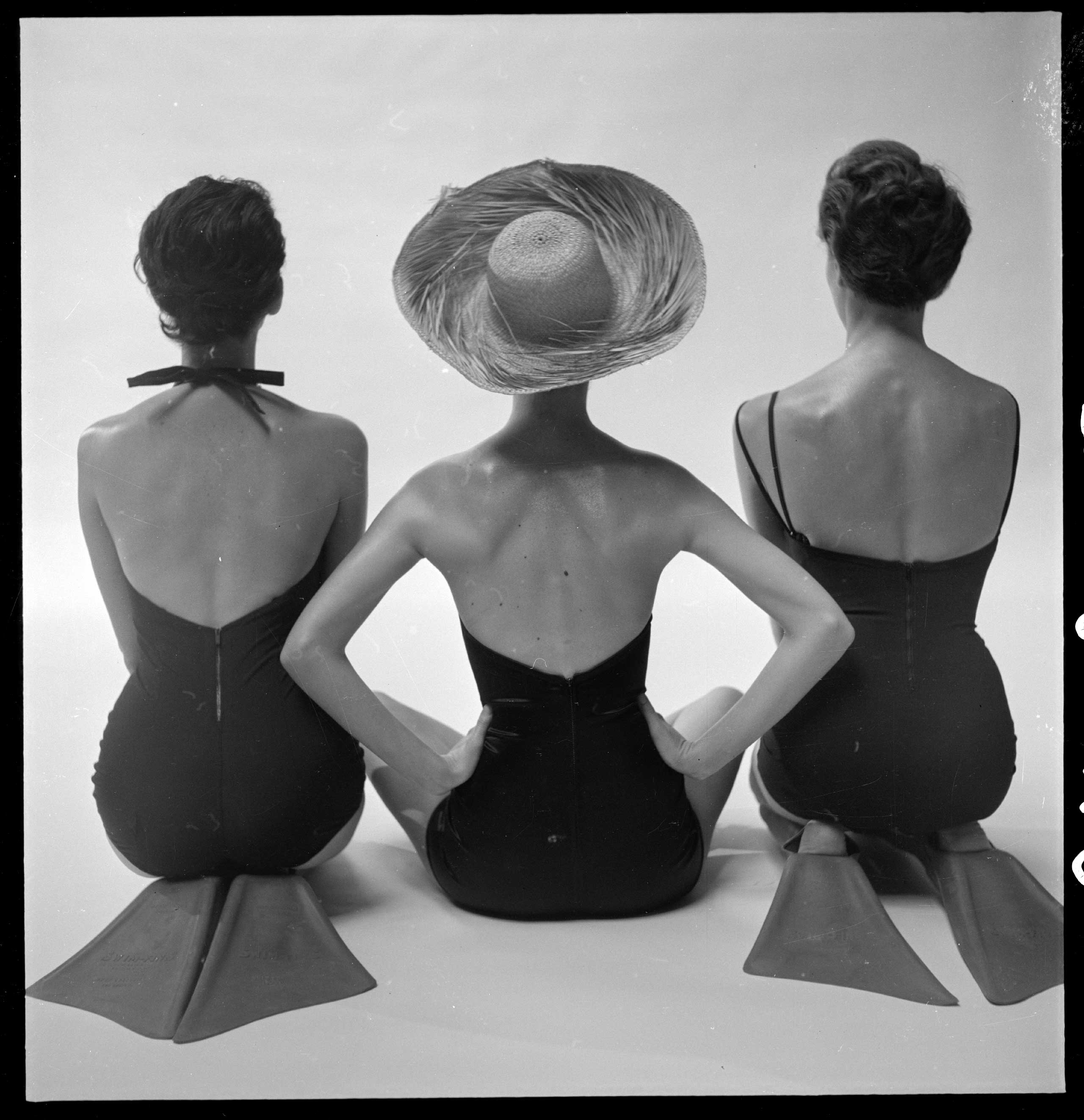 Back view of fashion models in swim suits, two kneeling wearing swim fins, and one seated. Published in Harper's bazaar, Jan. 1950.