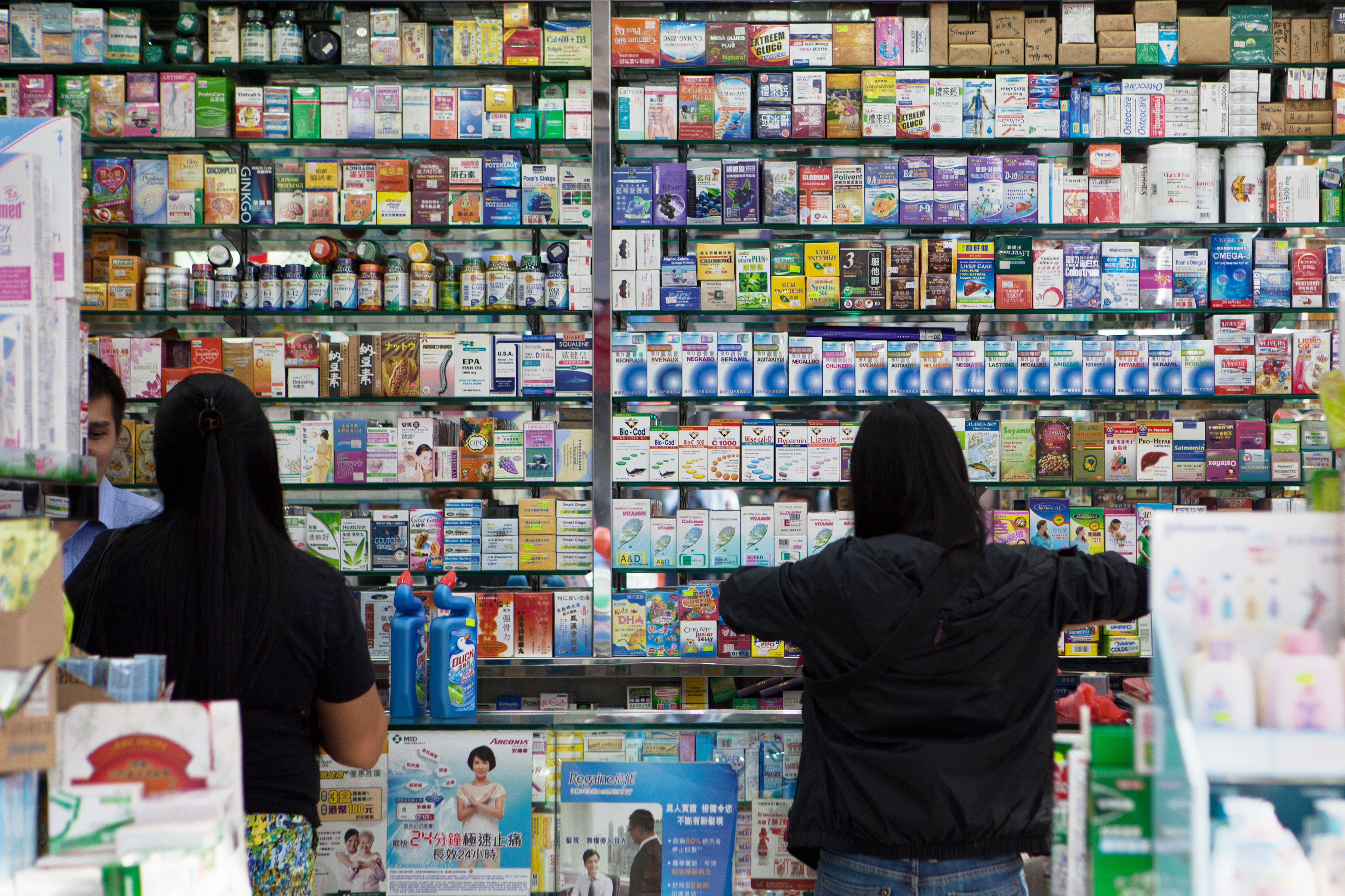 This picture taken on Nov. 18, 2013, shows customers buying goods in an independent pharmacy in Hong Kong. Safety fears over medication in mainland China are driving a risky illegal trade in cancer drugs in Hong Kong, experts say