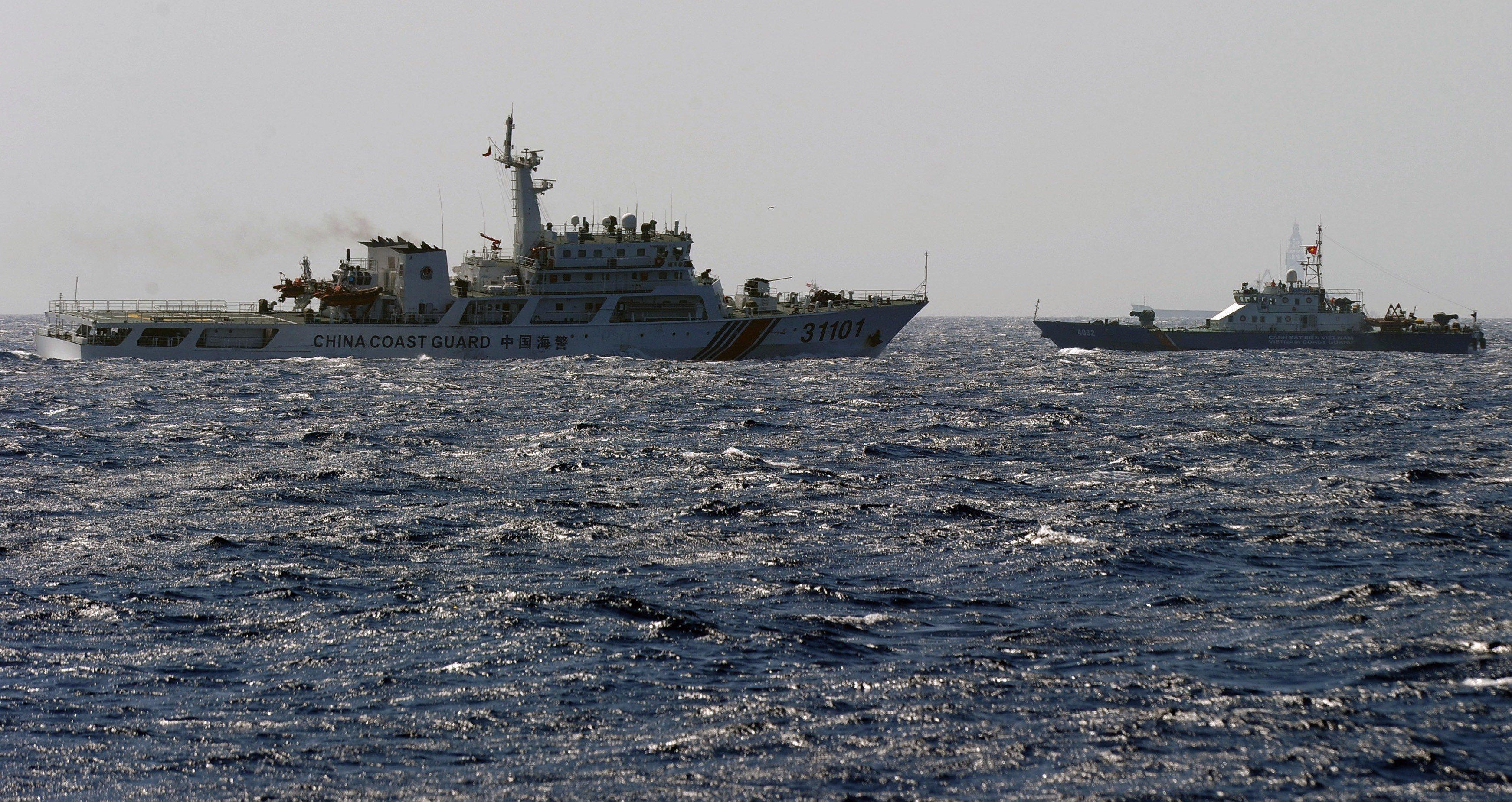 This picture taken on May 14, 2014 shows a China Coast Guard ship (L) chasing a Vietnam Coast Guard vessel near the site of a Chinese drilling oil rig in disputed waters in the South China Sea.
