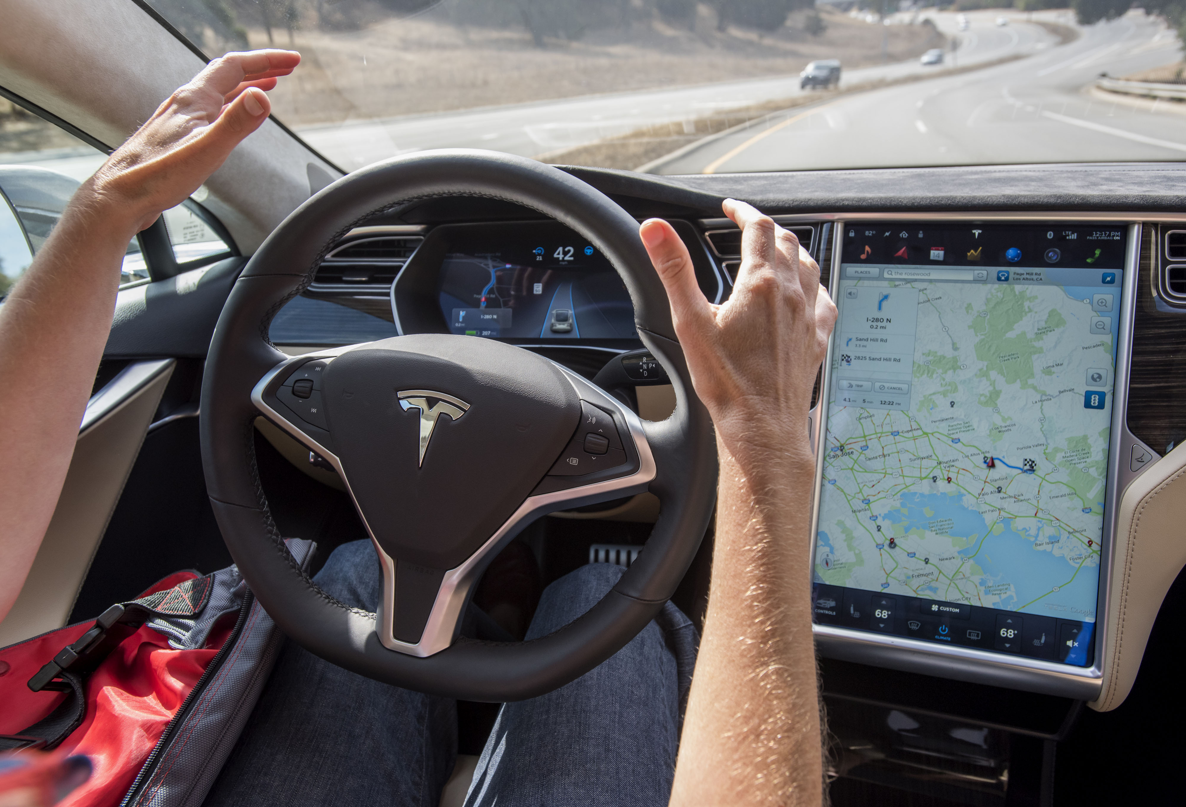 In this Oct. 14, 2015 file photo, a member of the media test drives a Tesla Model S car equipped with Autopilot in Palo Alto, California, U.S.
