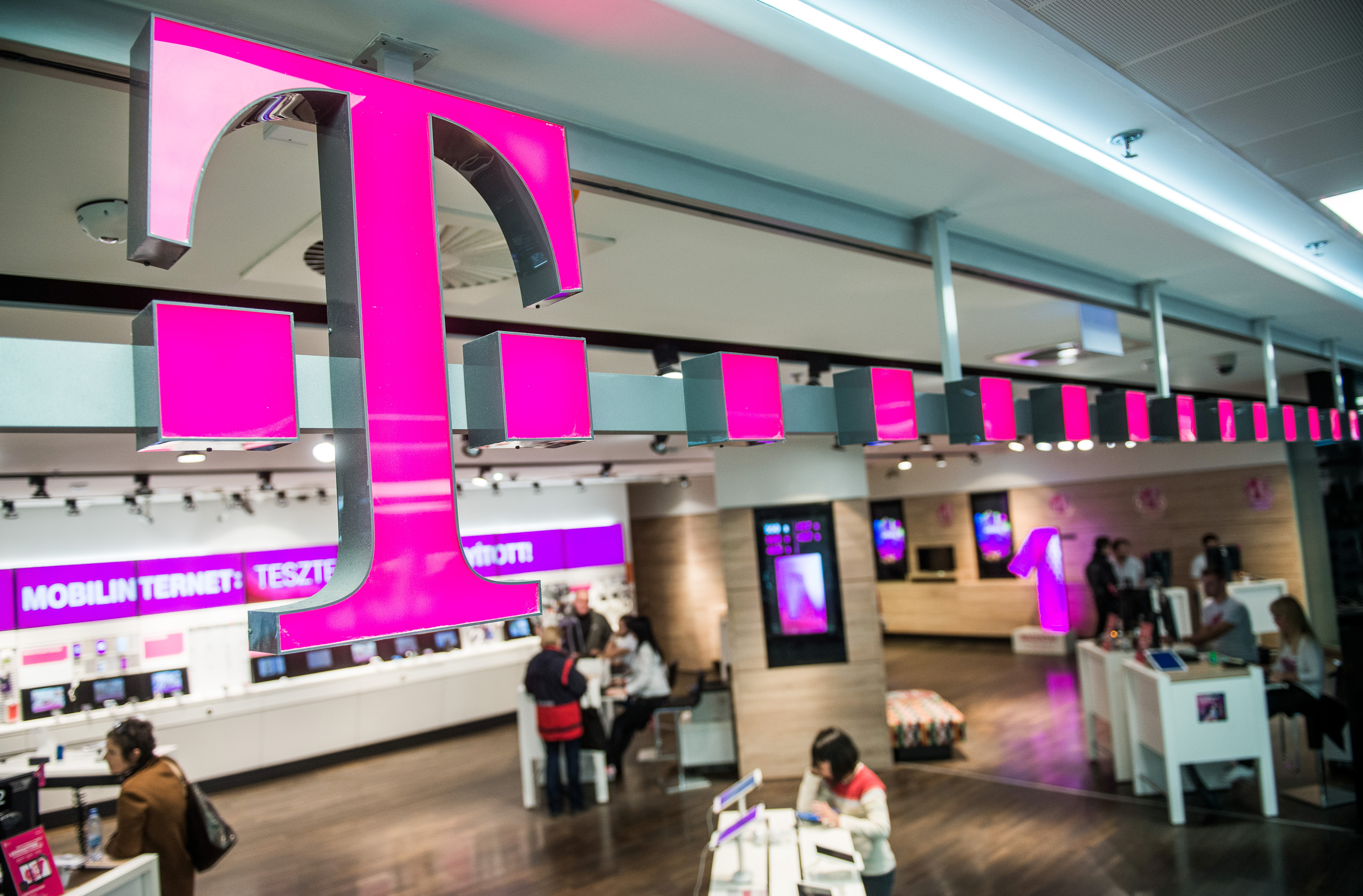 Customers browse mobile phone handsets as a sign sits above the entrance to a T-Mobile store, operated by Magyar Telekom Nyrt., in Budapest, Hungary, on Monday, Nov. 2, 2015.