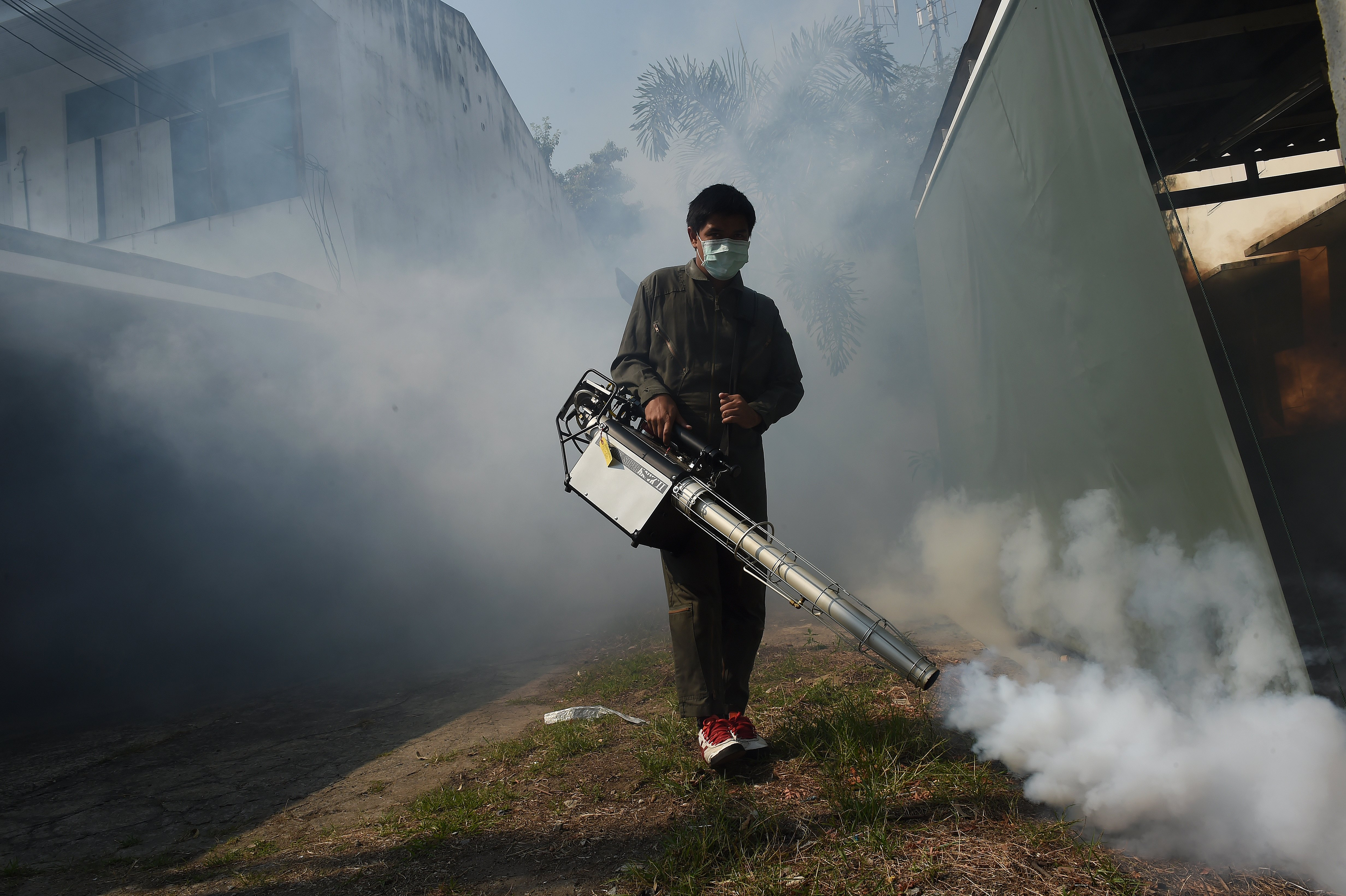 A municipal worker fumigates a residential area in Bangkok against the Aedes aegypti mosquito, carrier of Dengue and Zika virus, Bangkok on February 5, 2016.