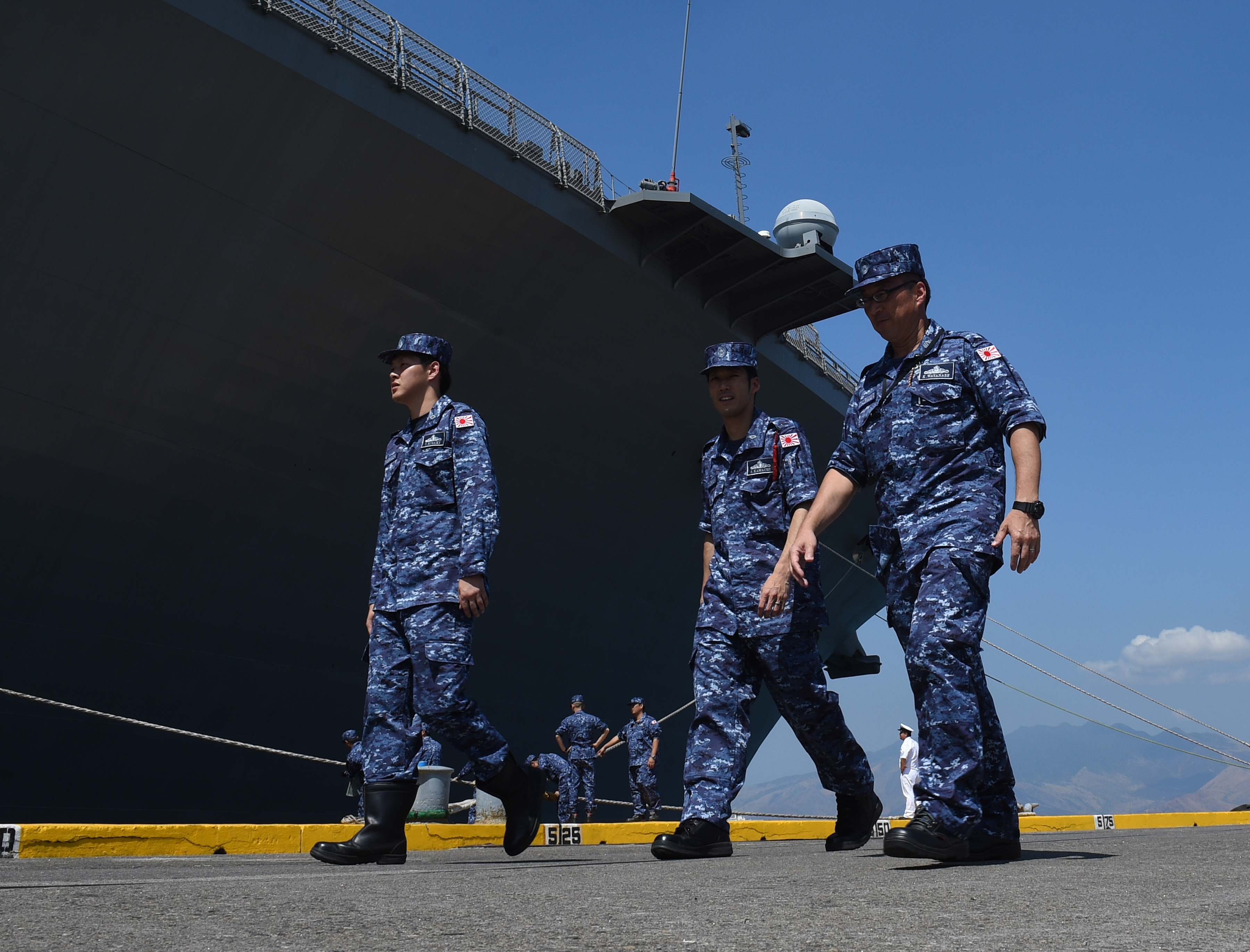 Sailors of Japanese helicopter carrier Ise patrol past their ship shortly after arriving at the former U.S. naval base, Subic port, north of Manila, on April 26, 2016