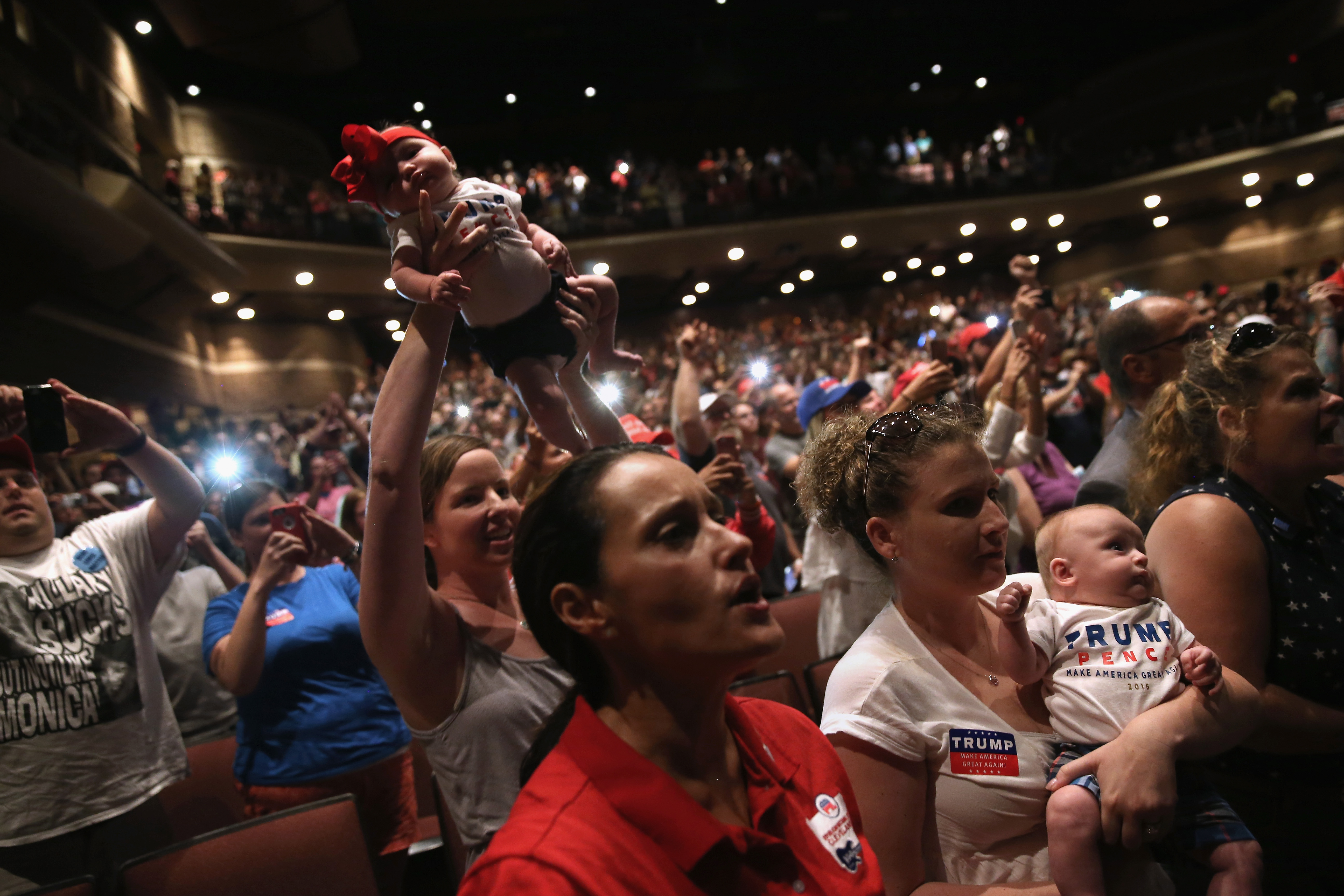 Women hold up their babies festooned for Republican Presidential nominee Donald Trump as he speaks at a campaign rally in Mechanicsburg,  on August 1, 2016.