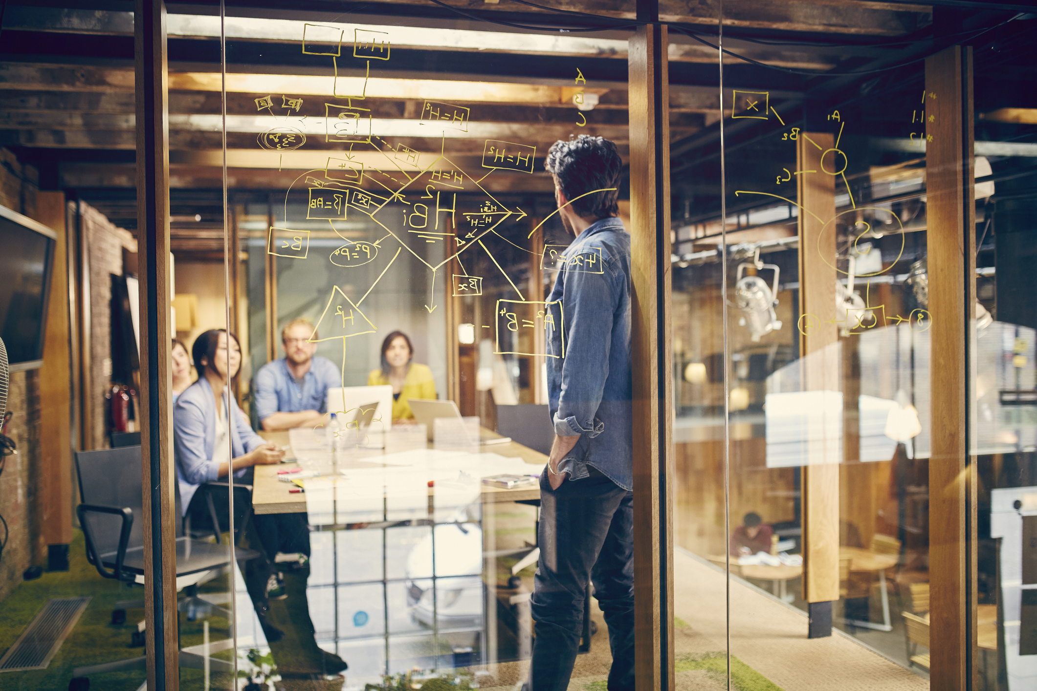 A team of young professionals discuss a project in modern office meeting room.