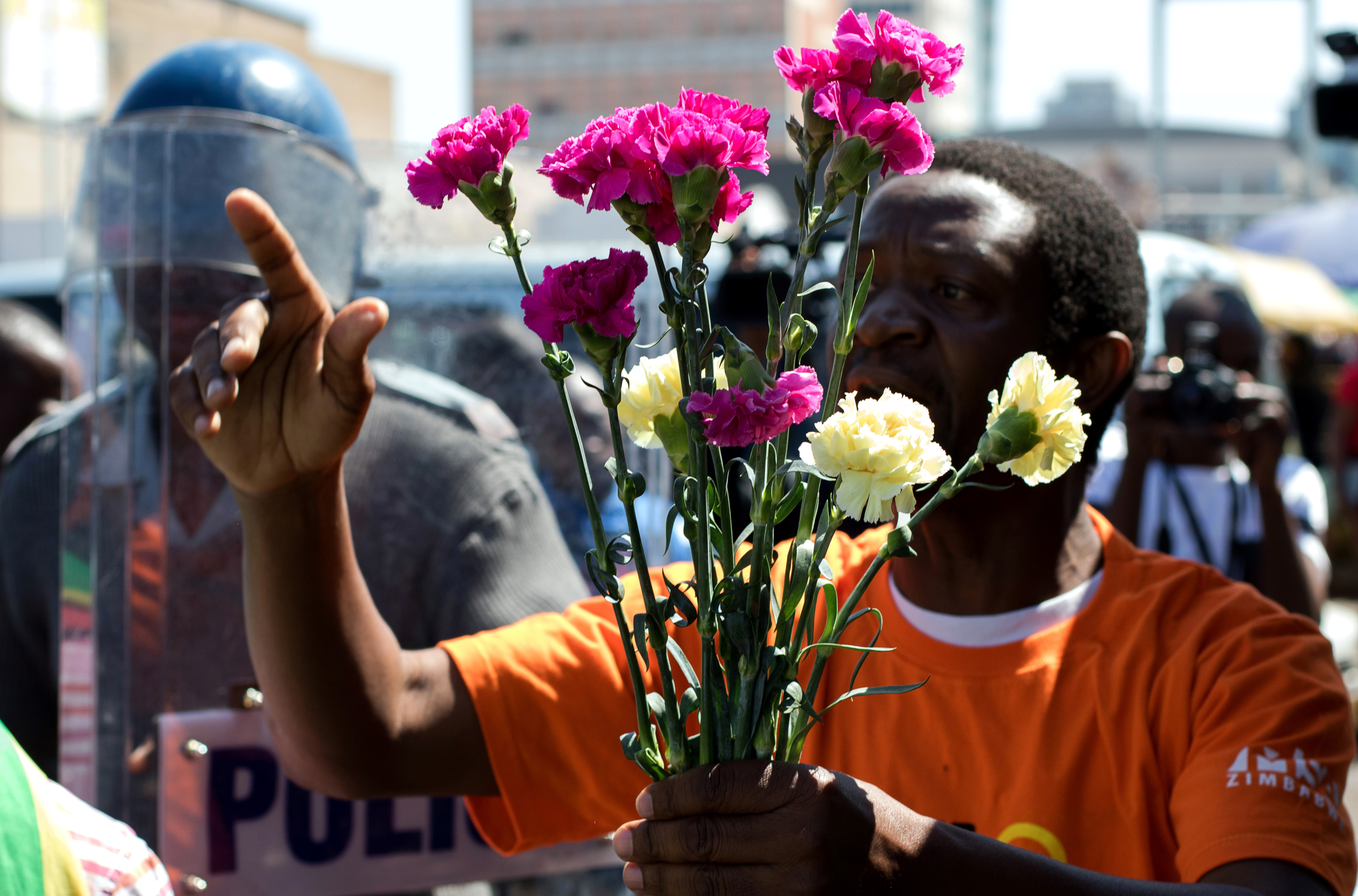 Zimbabwe activist Stan Zvorwadza offers flowers to antiriot policemen at Harare Central Police Station during a protest action on Aug. 18, 2016