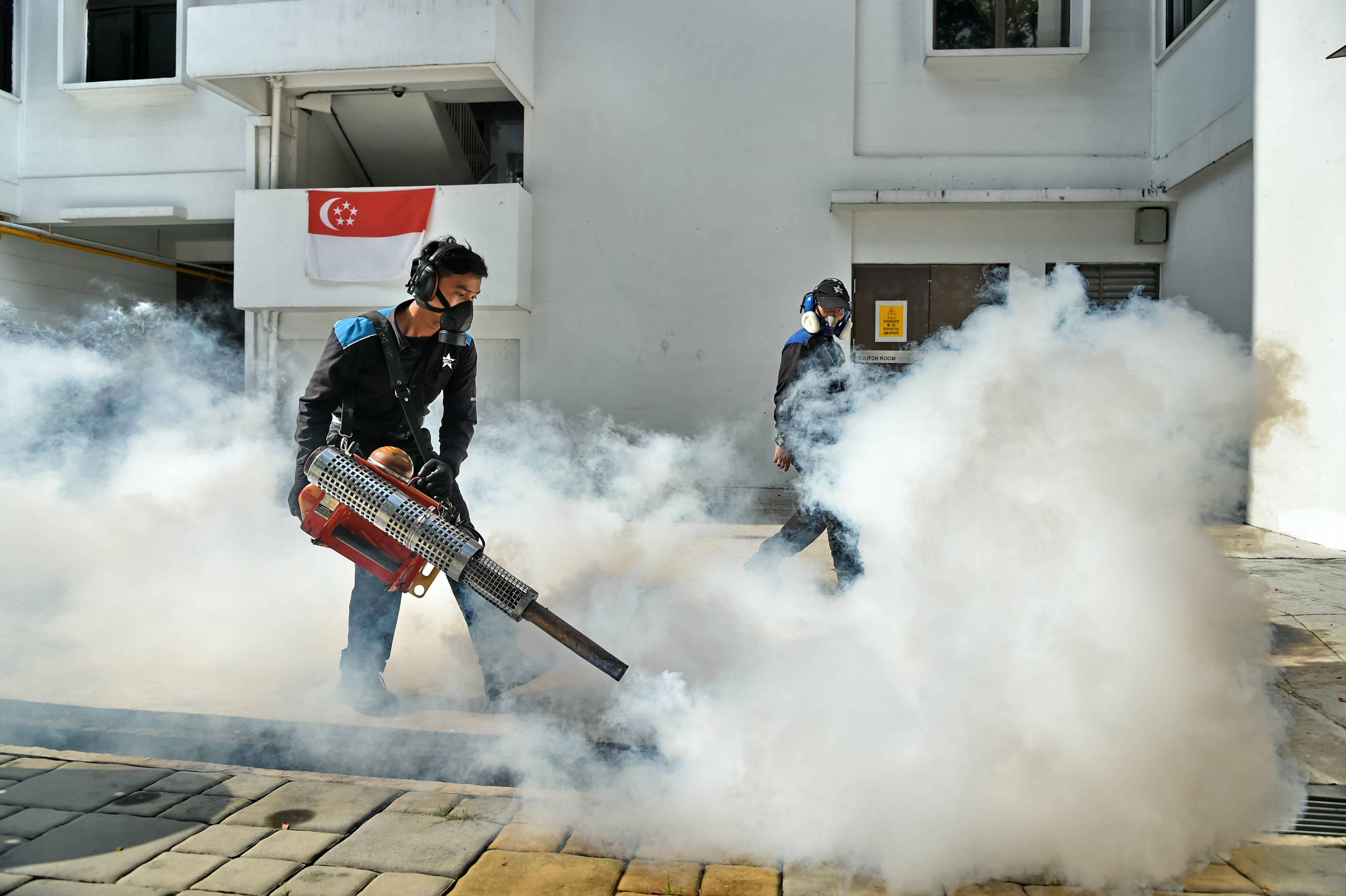 Pest control staff fumigate the drainage at the Macpherson neighbourhood housing estate in Singapore on August 31, 2016.