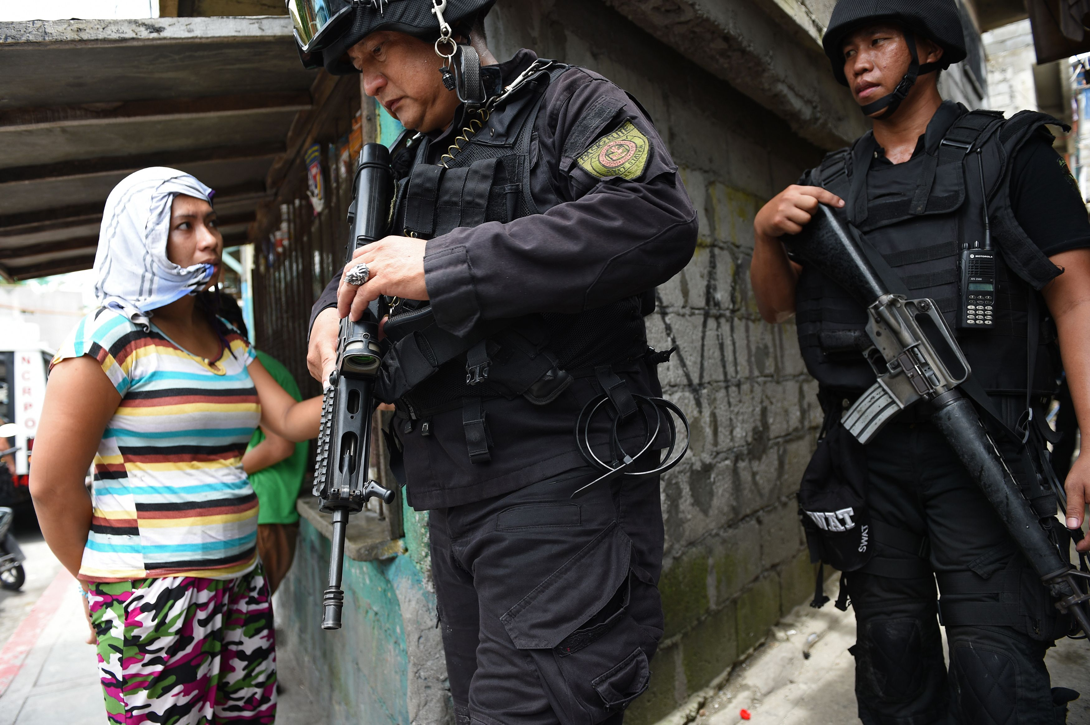 Police Special Weapons And Tactics (SWAT) personnel walk past a resident after an operation against illegal drugs in Pasig City, suburban Manila on September 5, 2016.