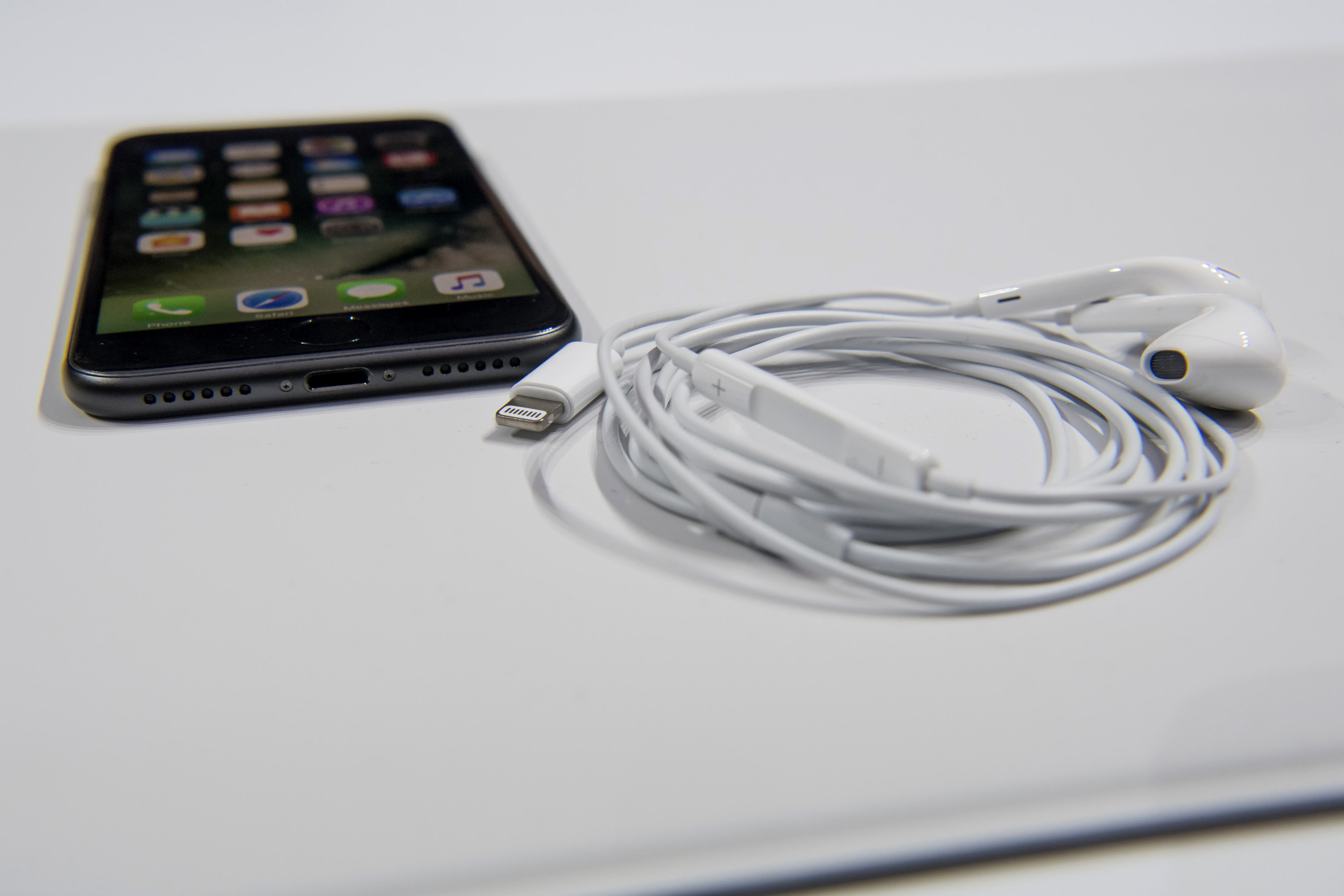 Apple Inc. EarPods headphones with lightning connection is displayed next to an iPhone 7 Plus during an event in San Francisco, California, U.S., on Wednesday, Sept. 7, 2016.