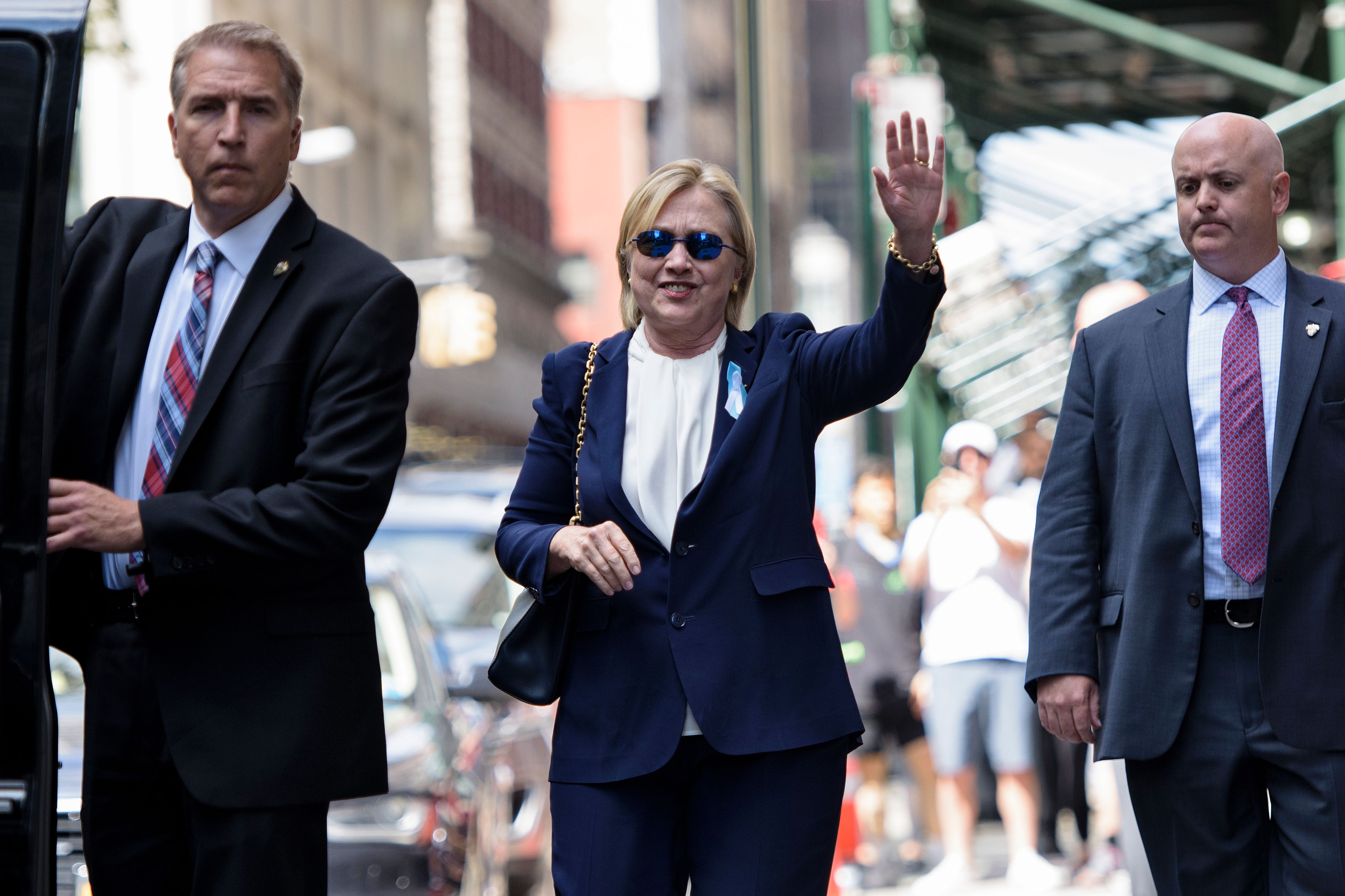 US Democratic presidential nominee Hillary Clinton waves to the press as she leaves her daughter's apartment building after resting on September 11, 2016 in New York.