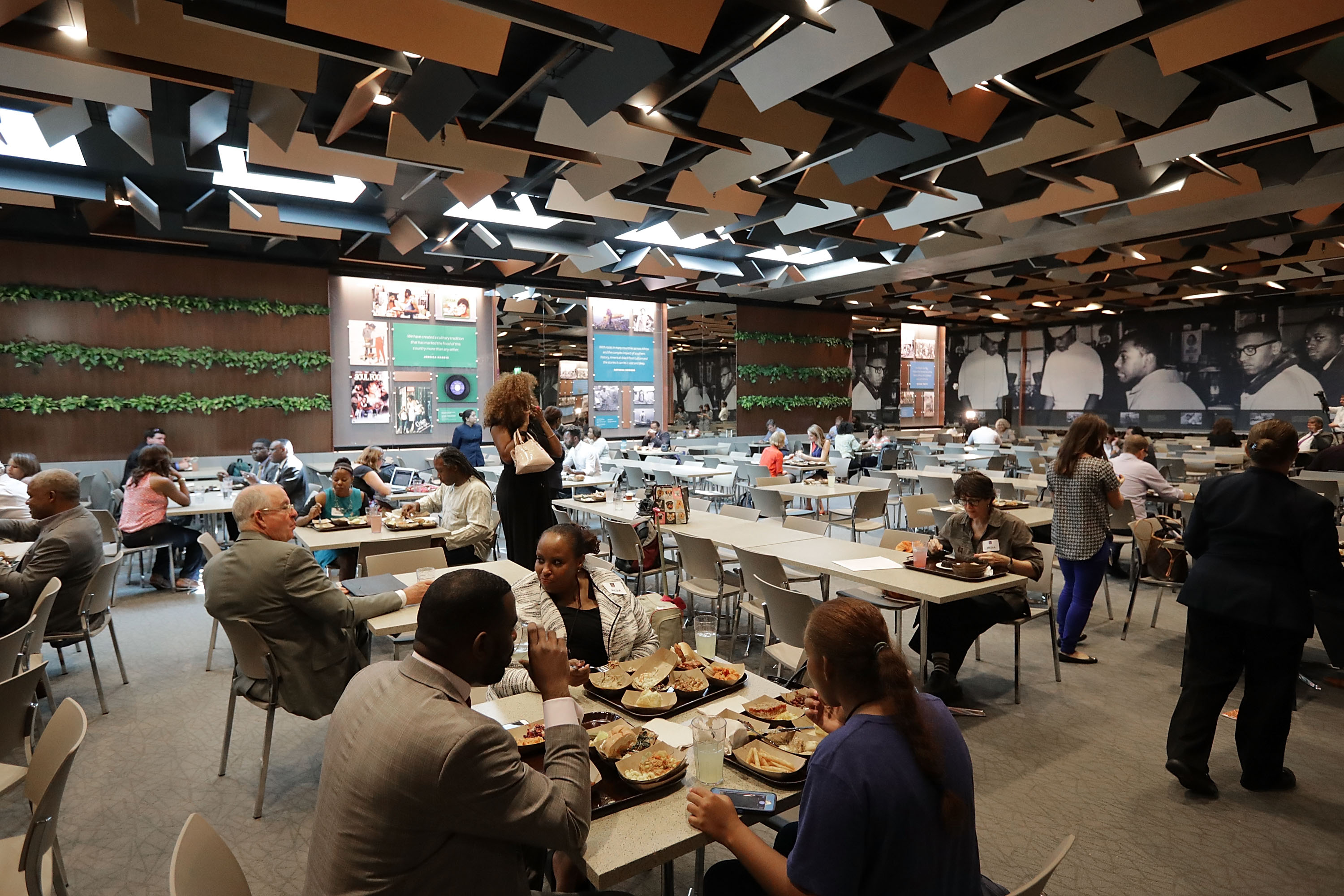 Guests sample dishes like Son-of-a-Gun stew, pan-roasted oysters, smoked haddock, corn croquettes with a gribiche sauce, slow cooked collards and other traditional foods at the Smithsonian's National Museum of African American History and Culture's Sweet Home Cafe Sept. 14, 2016 in Washington, D.C.